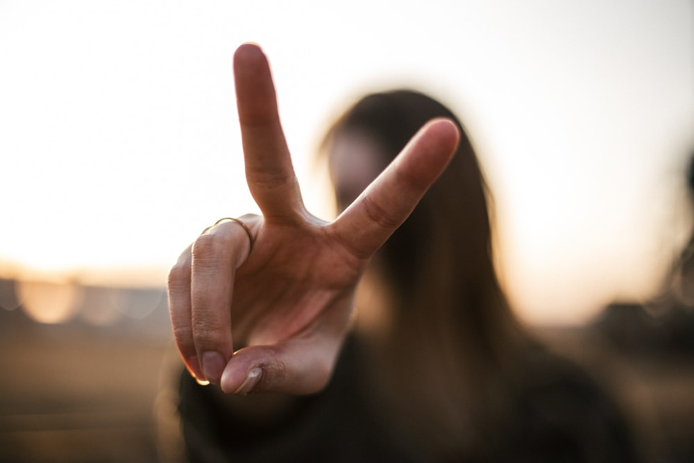 focus photography of woman hand with peace sign