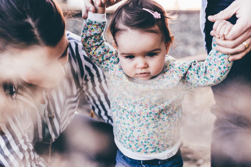 woman holding girl while learning to walk taken at daytime