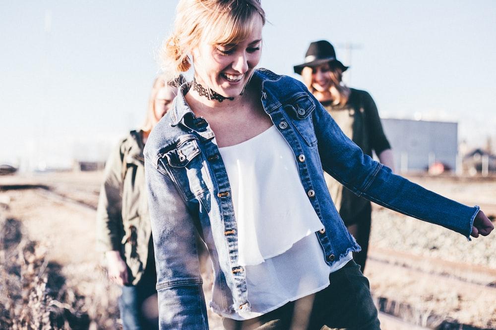 girl smiling wearing blue denim button-up jacket standing outdoor during daytime