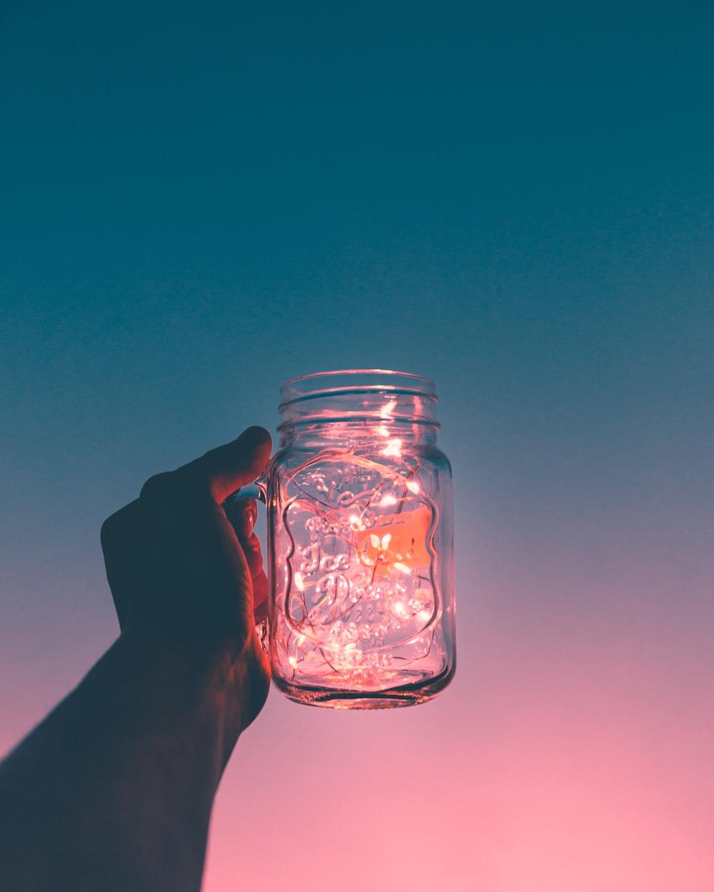 person holding clear glass mug jar