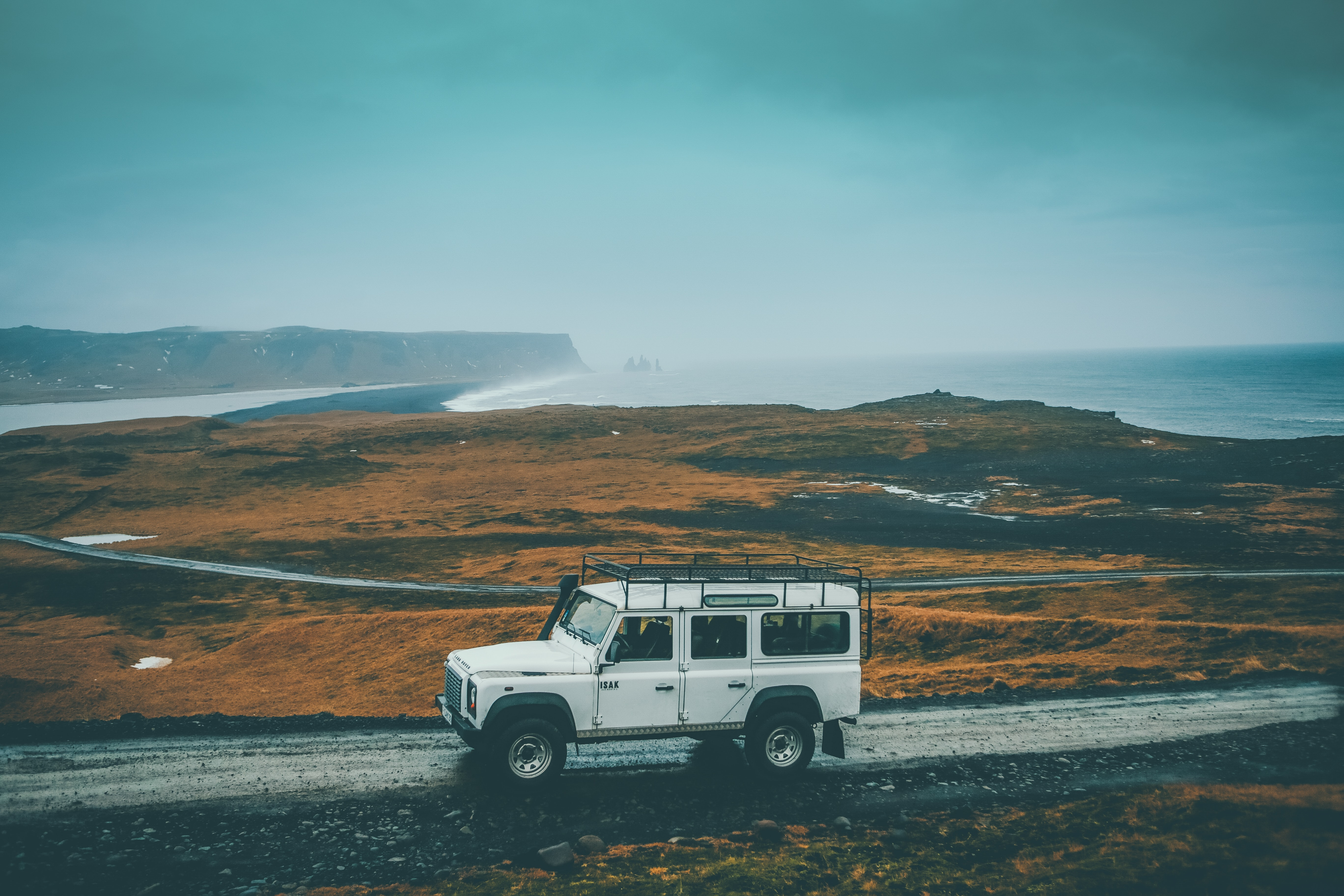 A white off-road vehicle on a dirt road with a misty shoreline at the back