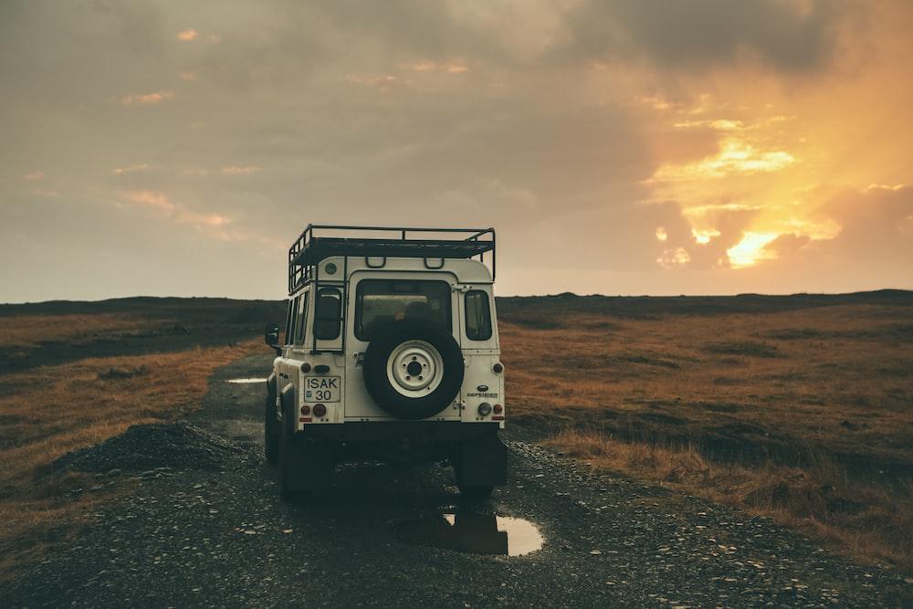 white wrangler on road during sunset