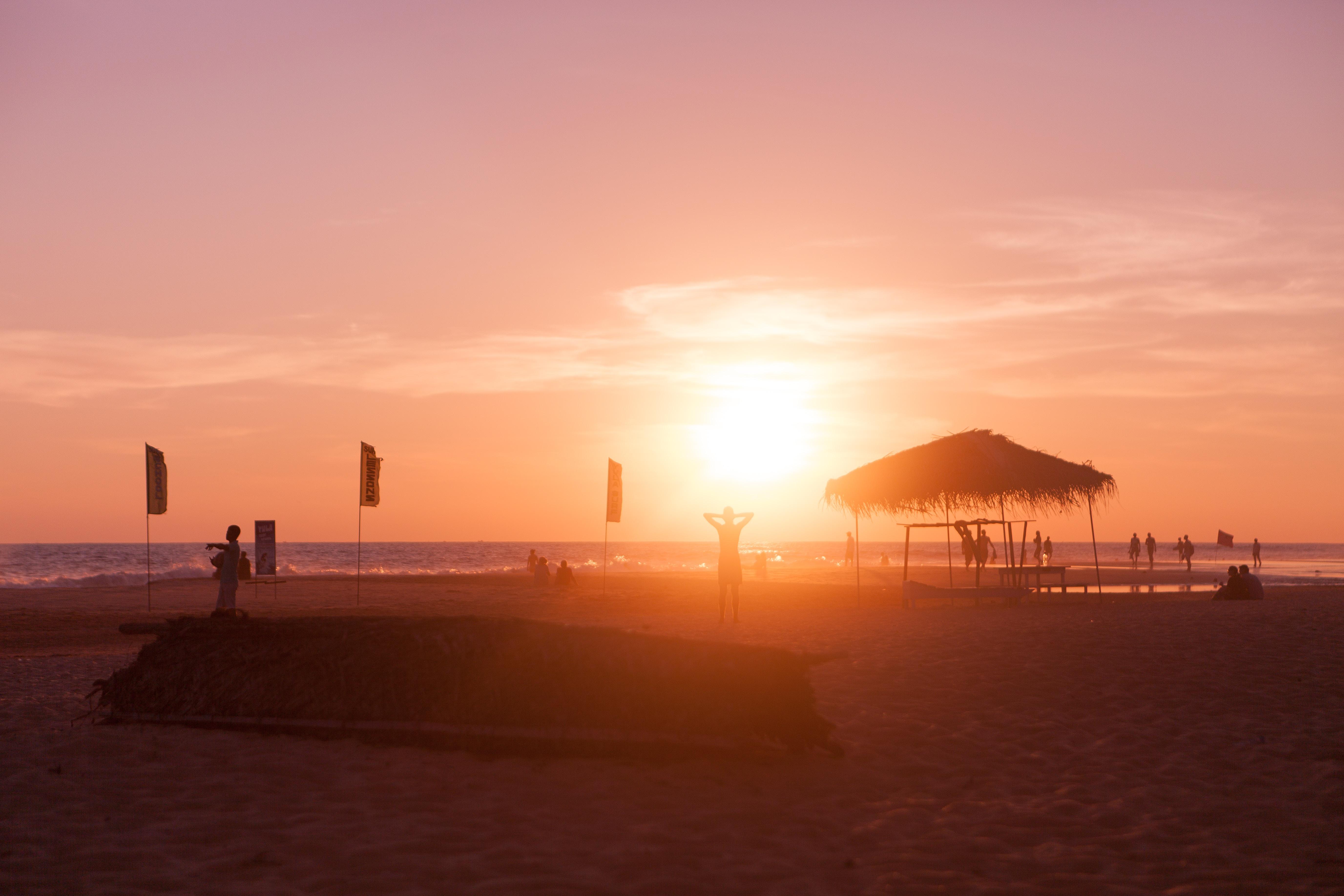 silhouette beach hut near seashore during sunset