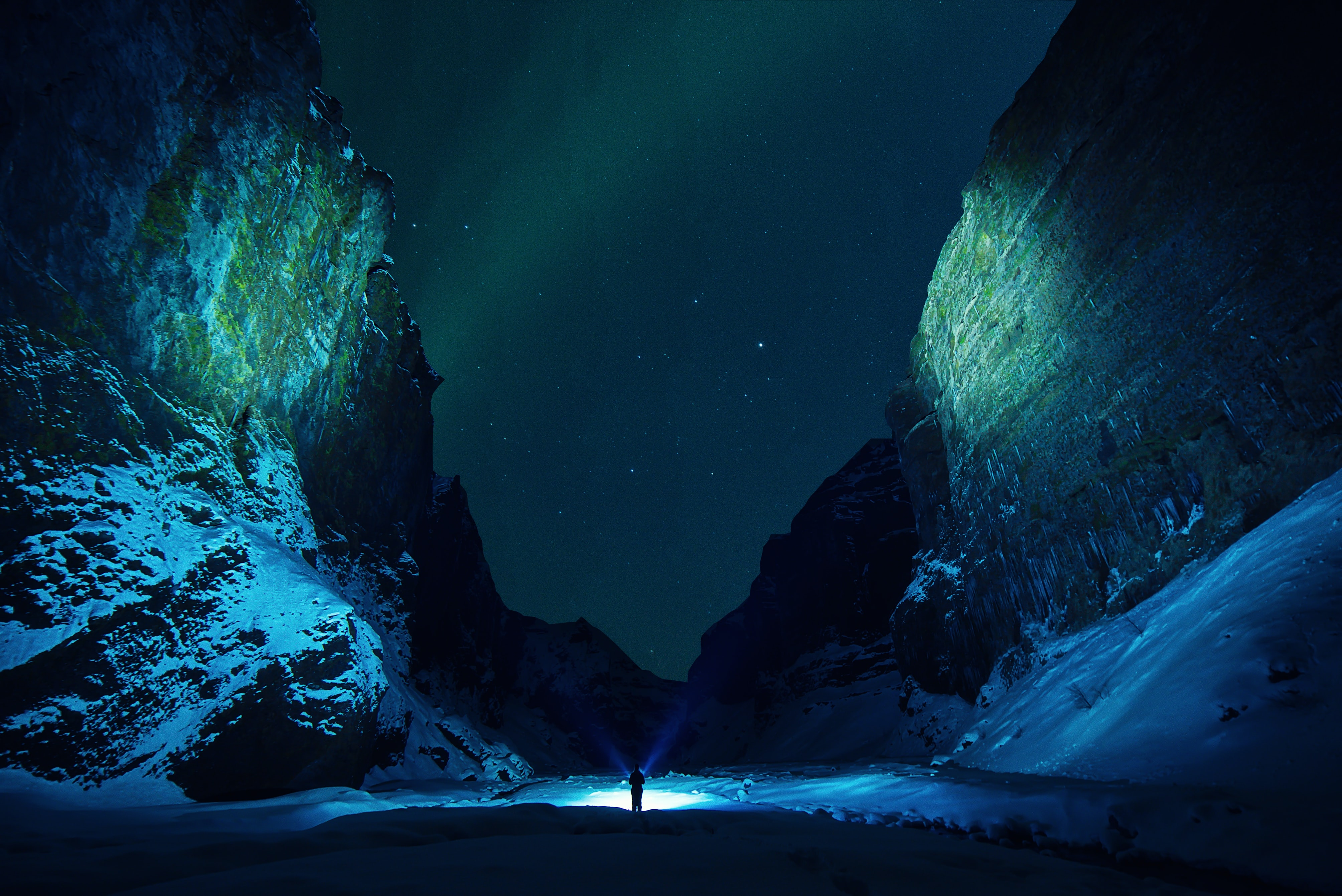 Iceland's Northern Lights fill the entirety of Stakkholtsgja Canyon and illuminates a silhouette of a person to the night sky