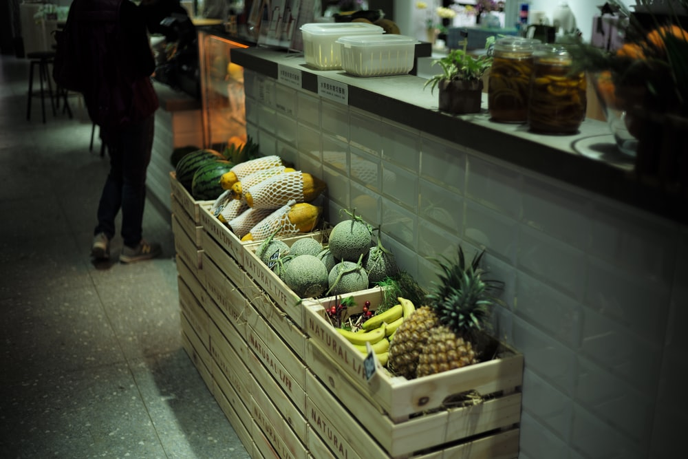 fruits in crates beside wall