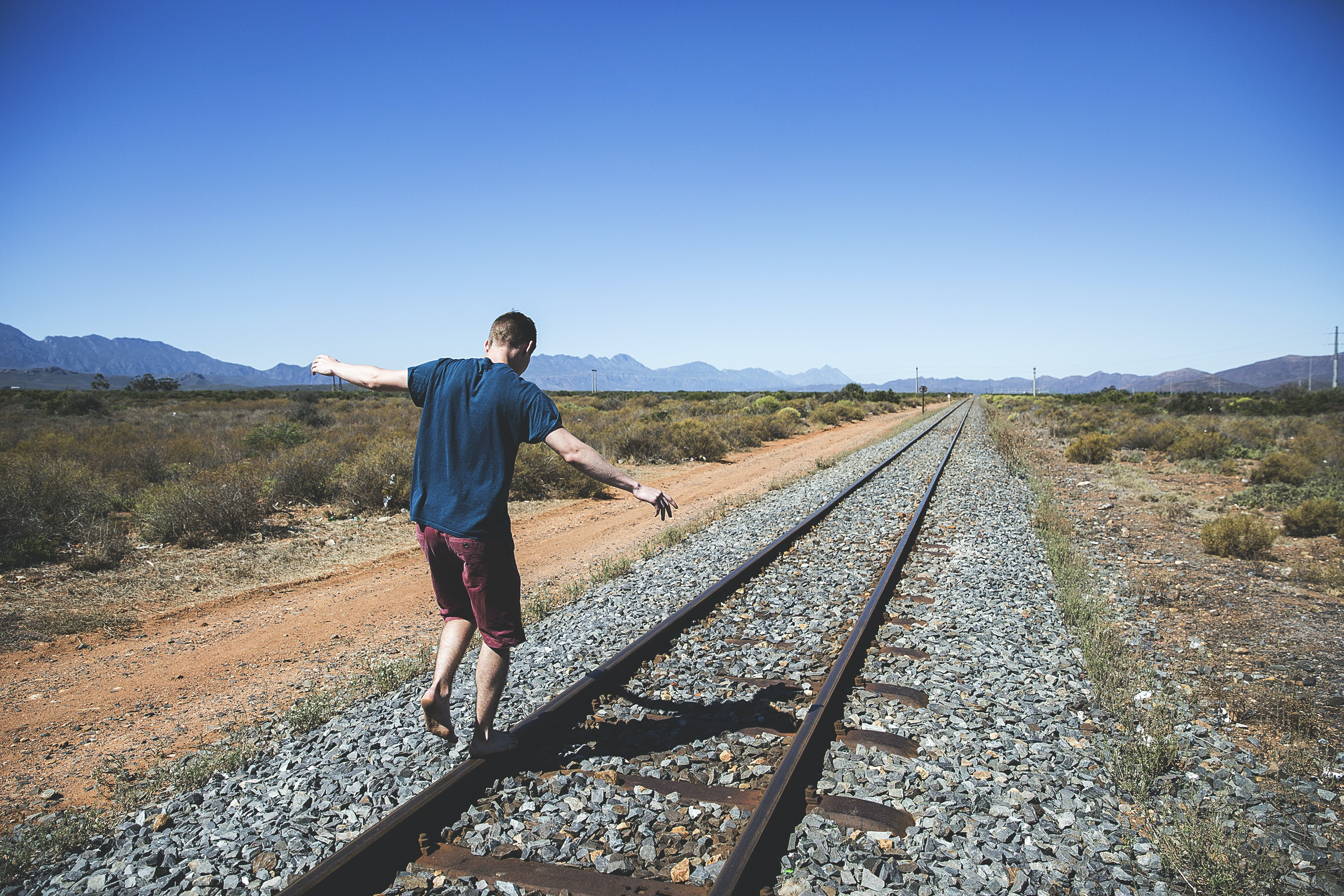 person walking on brown steel train rail outdoor during daytime