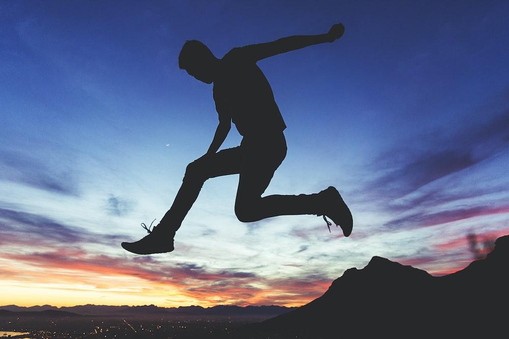 silhouette of man jumping near mountain