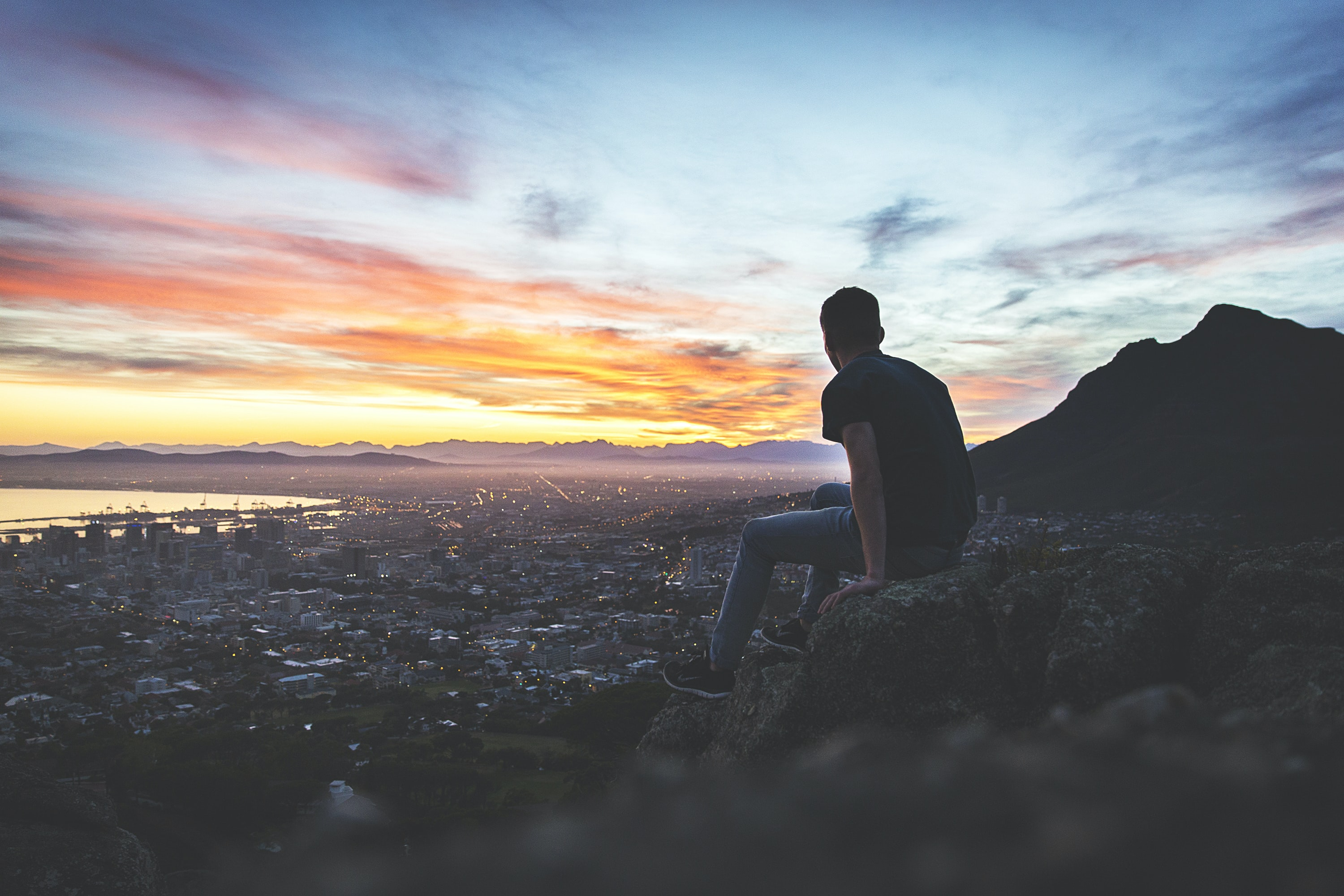 Man sitting on a rocky ledge, watching the sunset over Cape Town