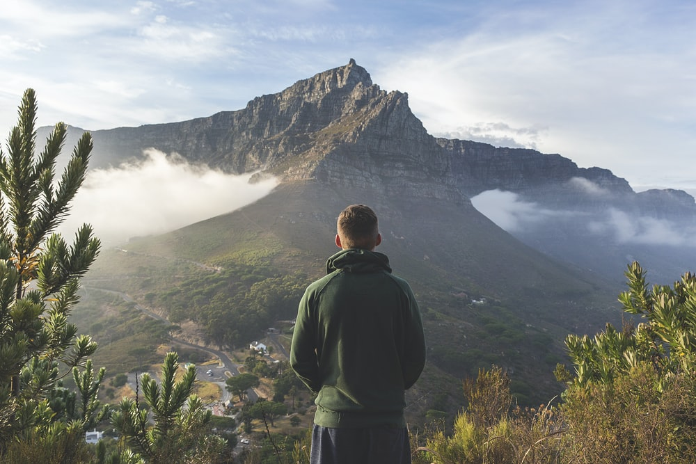 man standing in front of mountain
