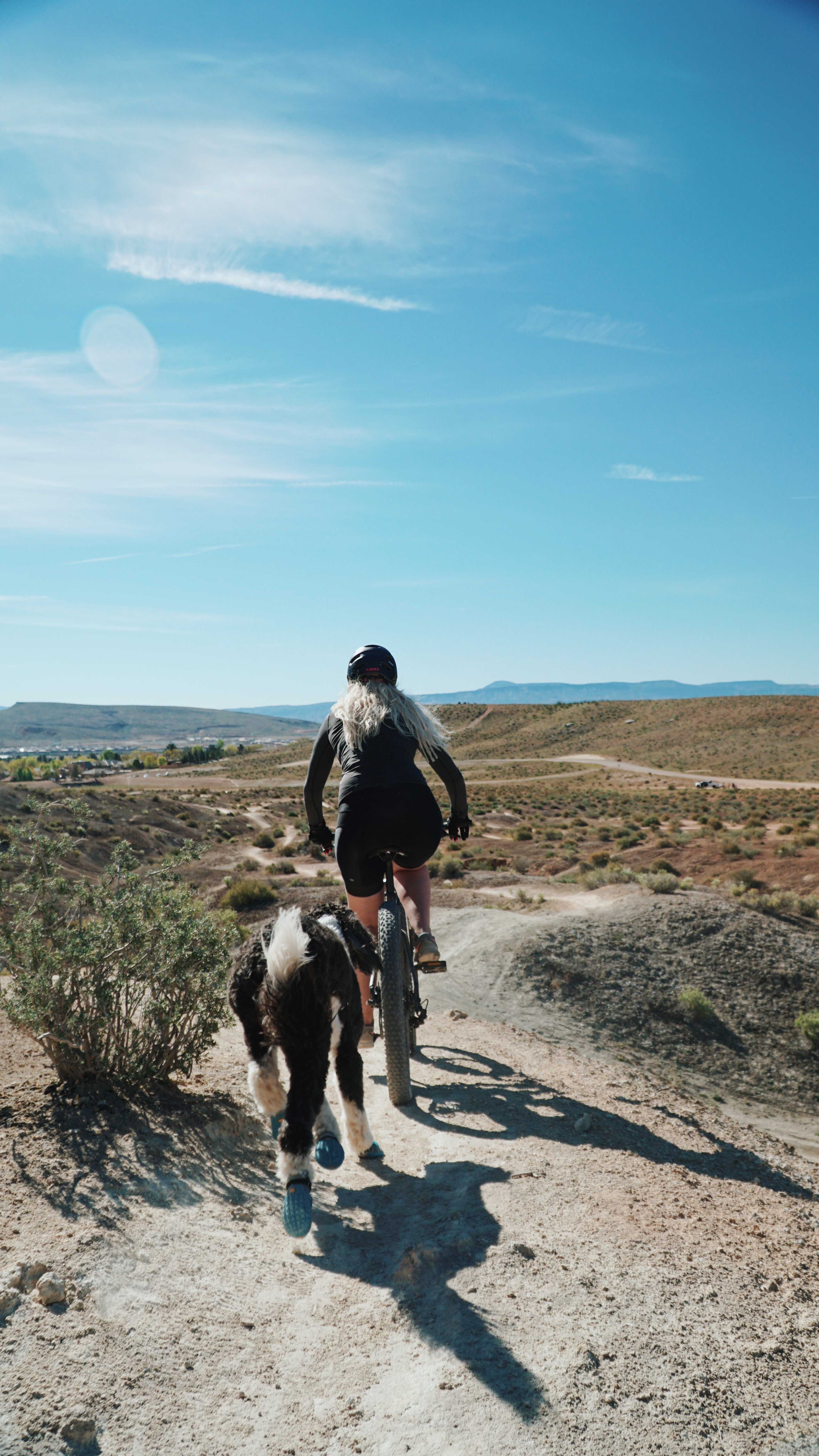 A blonde woman riding a bicycle through the desert with a dog following him in St. George