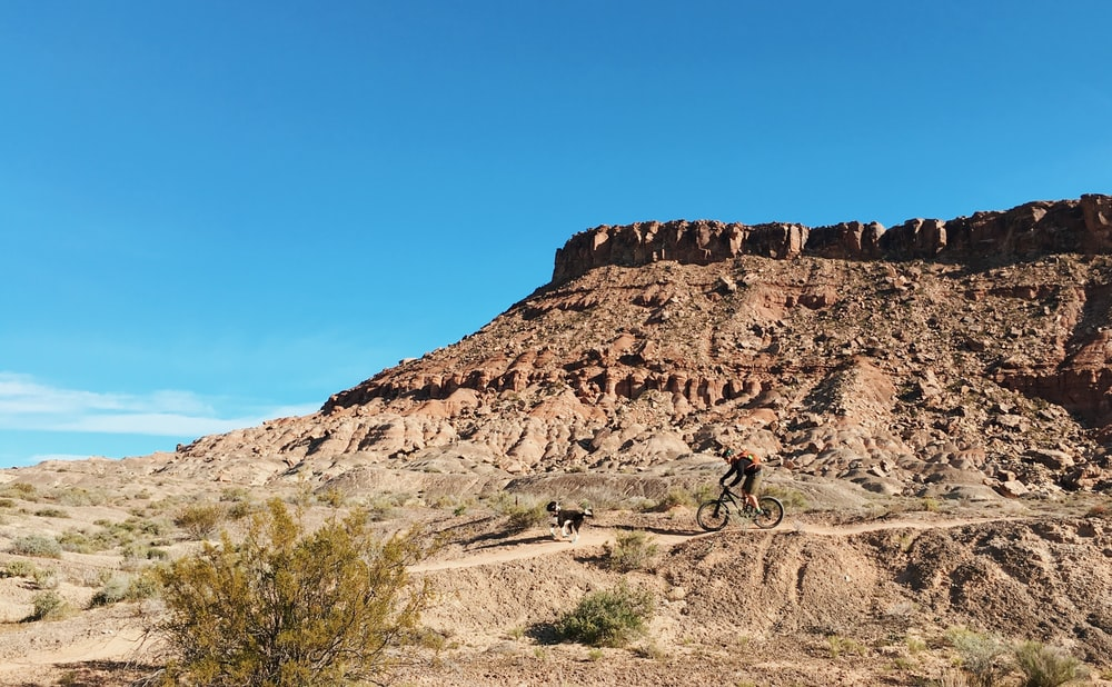 person riding bicycle near brown rock formation during daytime