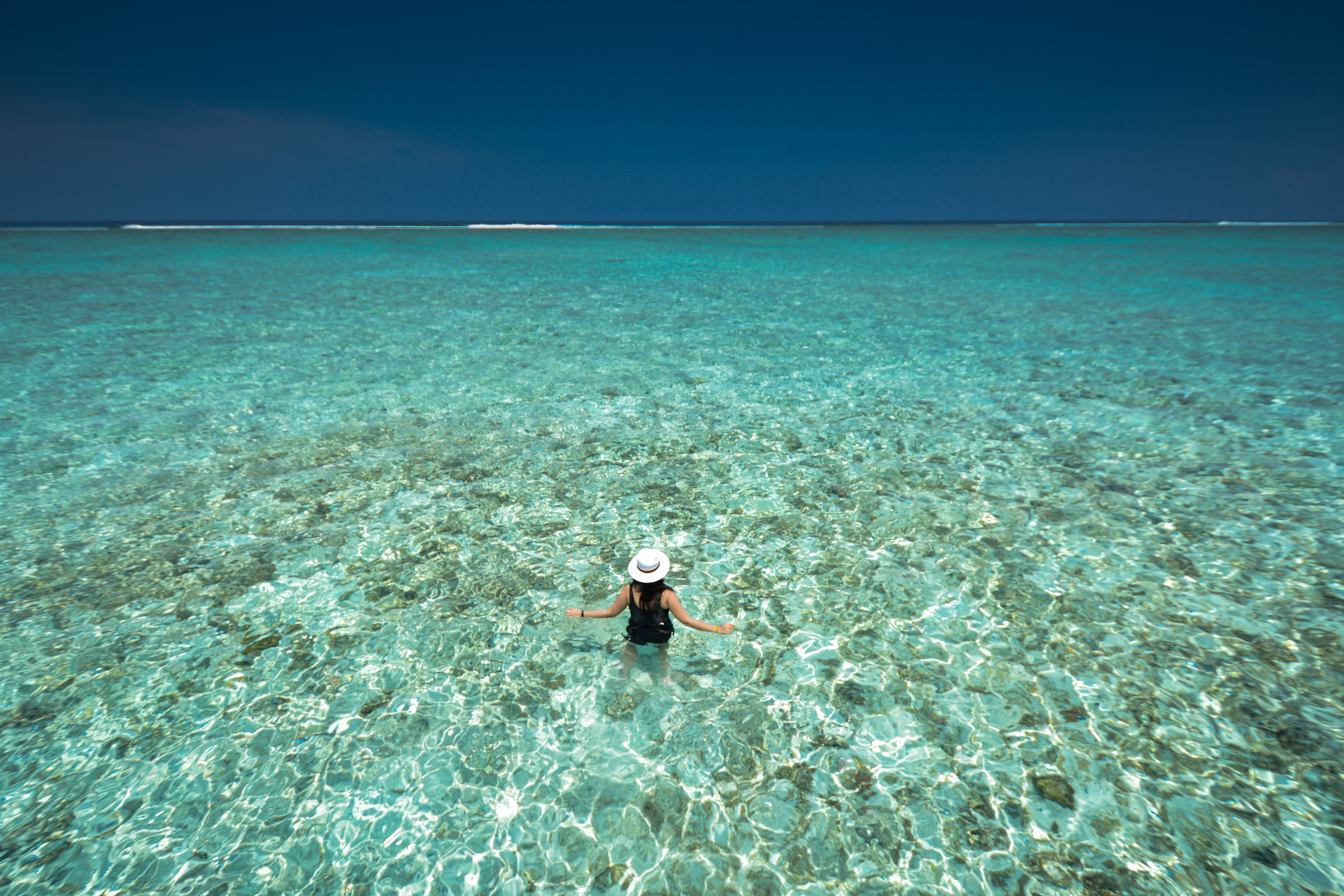 A woman in a white hat standing in clear waist-high water with the sea coast stretching far into the distance