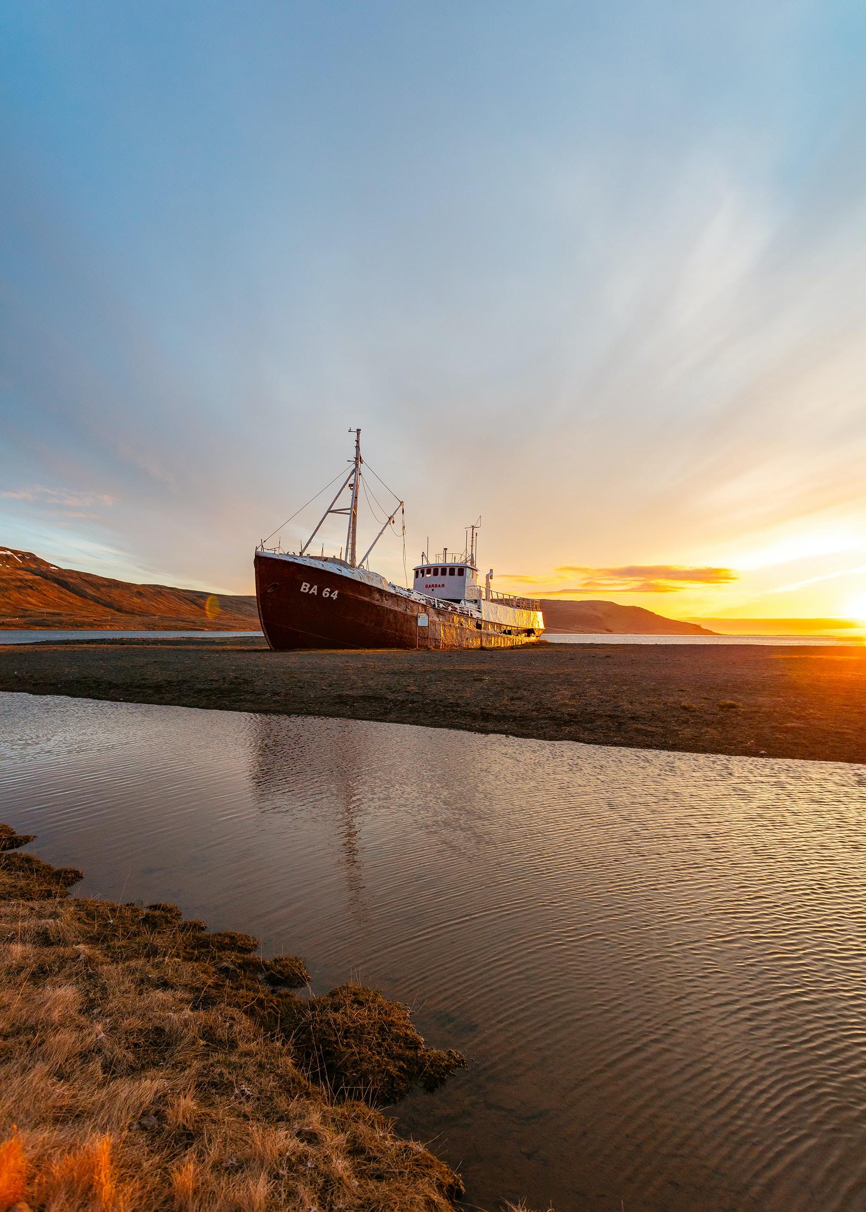 white and brown ship on seashore under sunrise