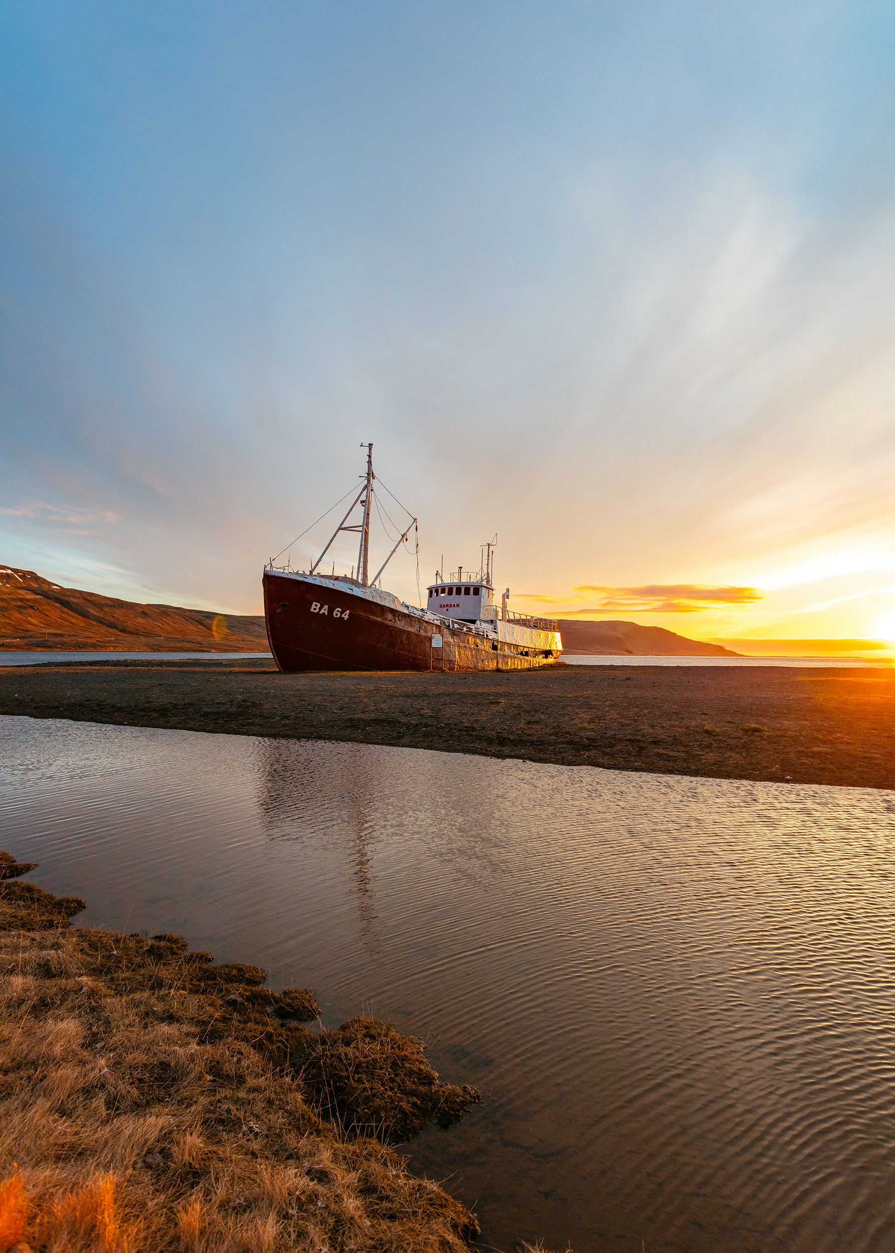 white and brown ship on seashore under sunrise
