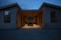 white wooden house with brown wooden picnic table inside at nighttime