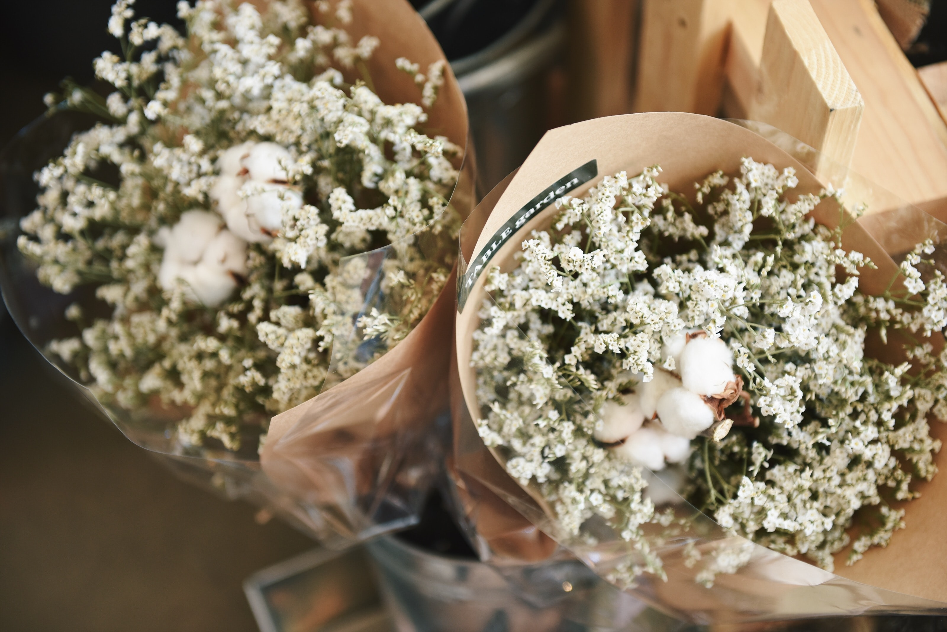Two large bouquets of baby's-breath flowers with cotton flowers in the middle wrapped in foil and paper