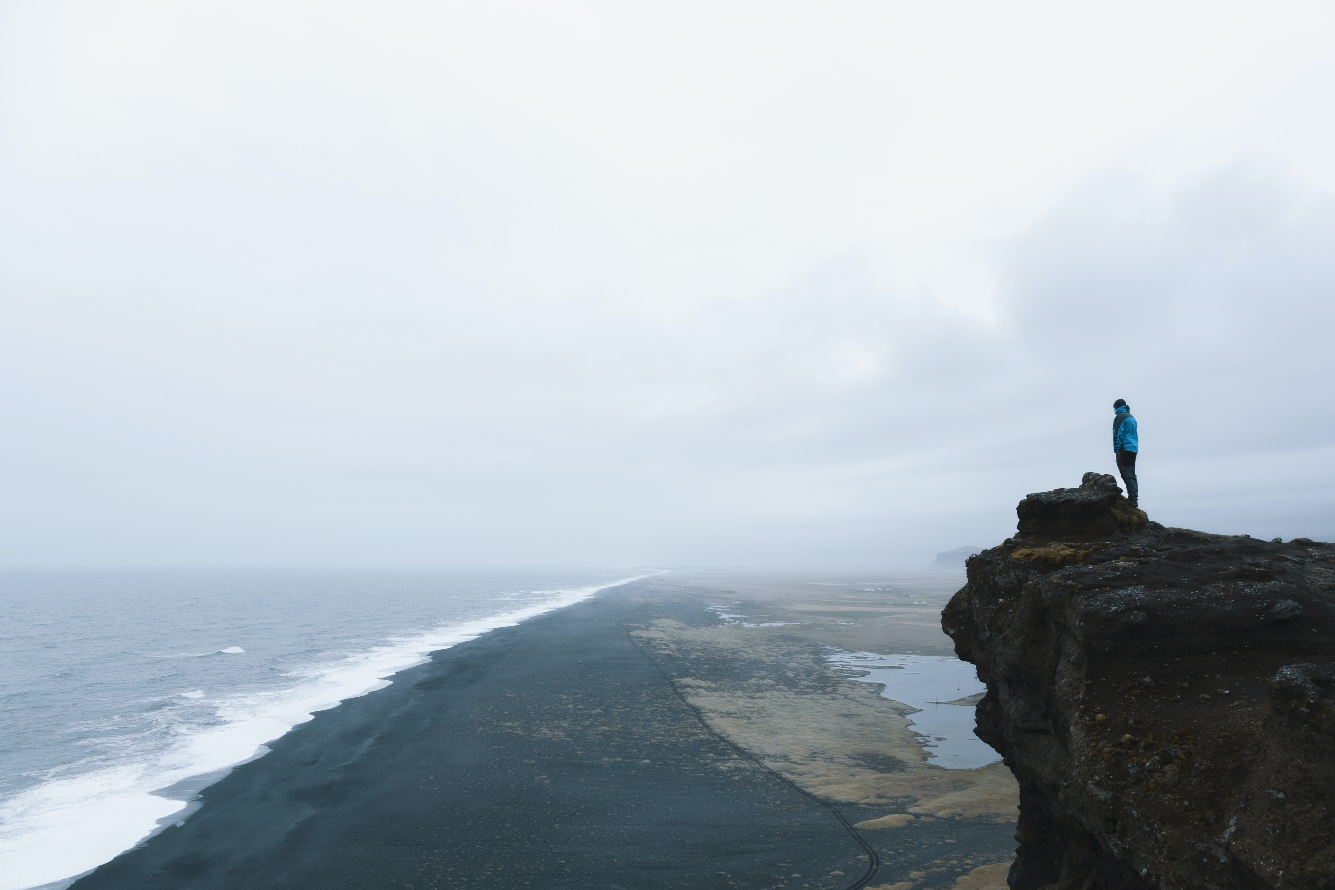 Man standing on a cliff overlooking a black sand shoreline in Vik