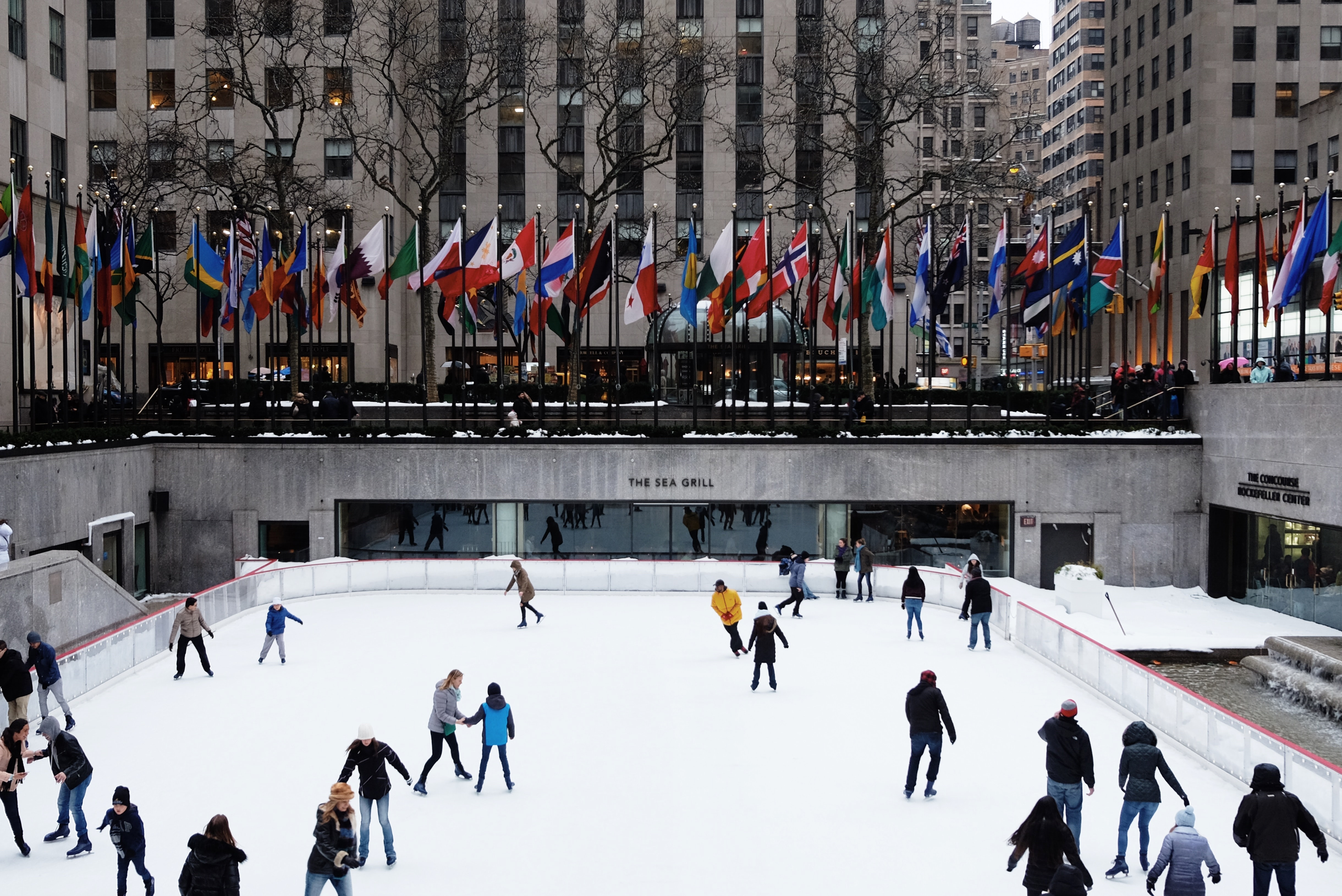 people ice skating on field surrounded by high-rise buildings