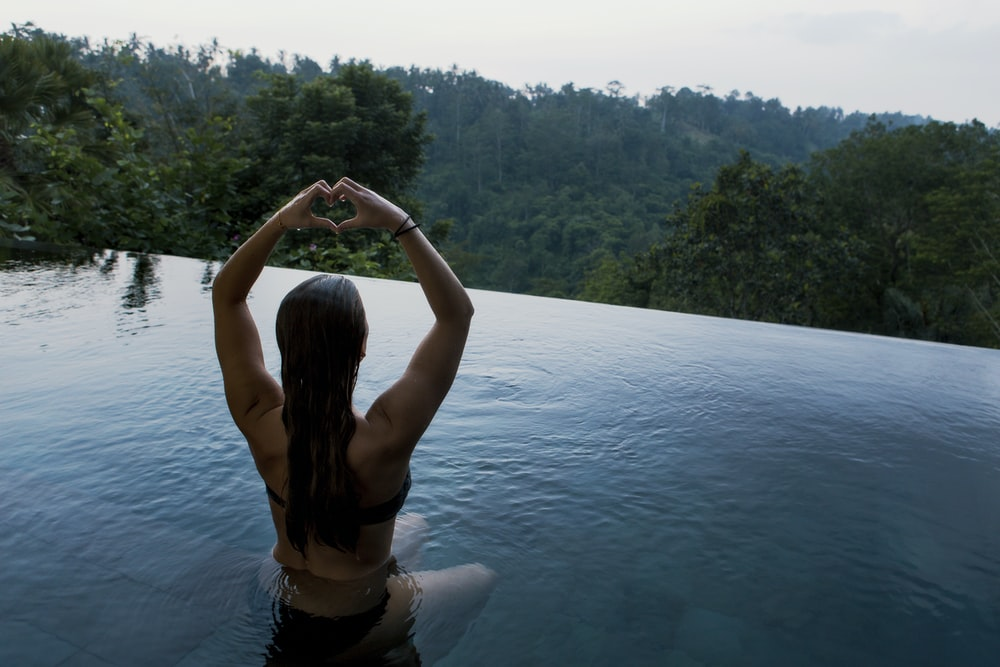 woman in infinity pool making heart hand gesture facing green leafed trees