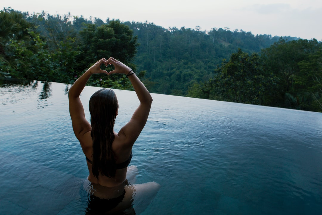 A woman meditating in an infinity pool overlooking a forest.