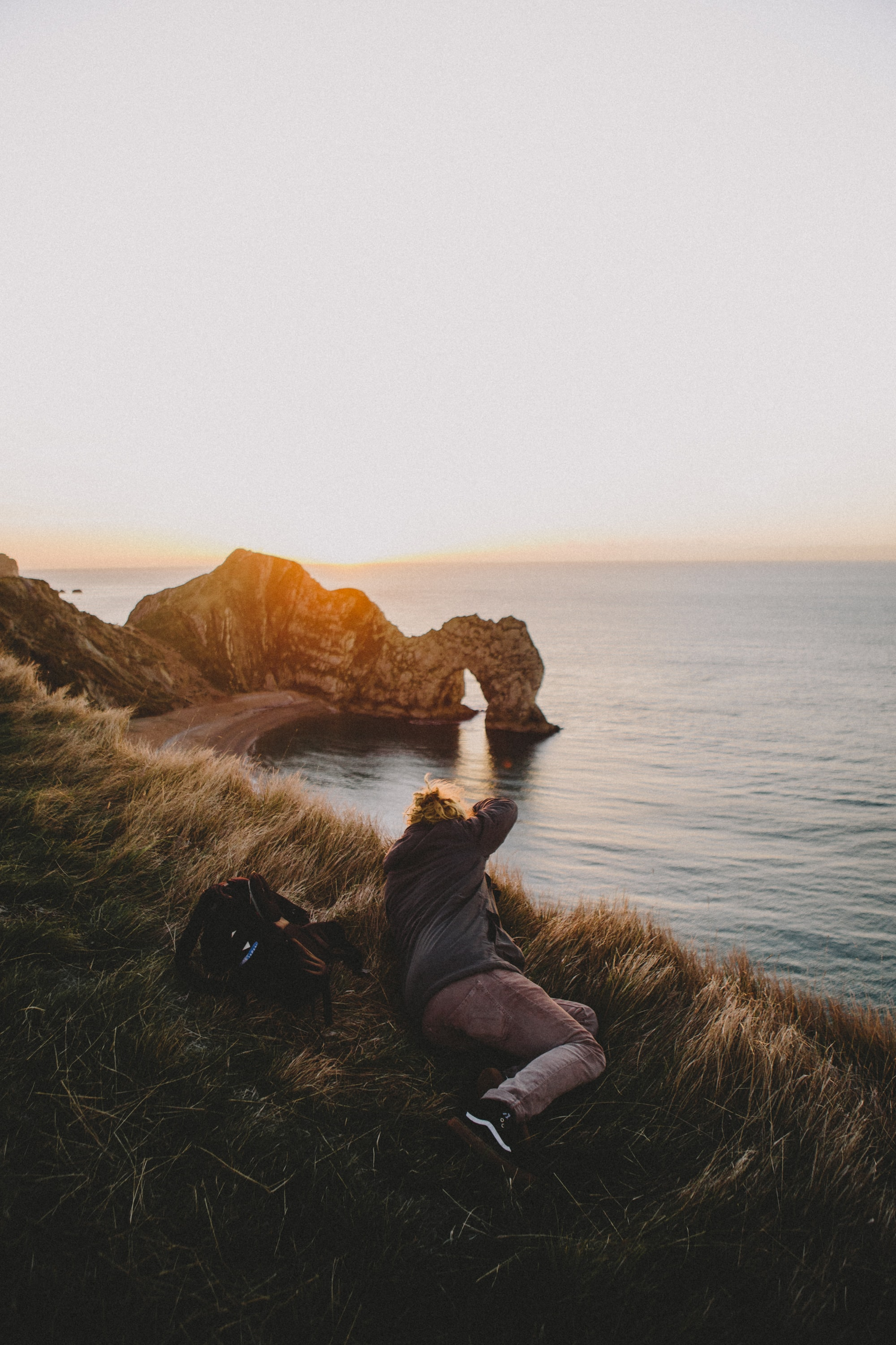 Photographer lying on the grass capturing the Durdle door arch on the cove during golden hour