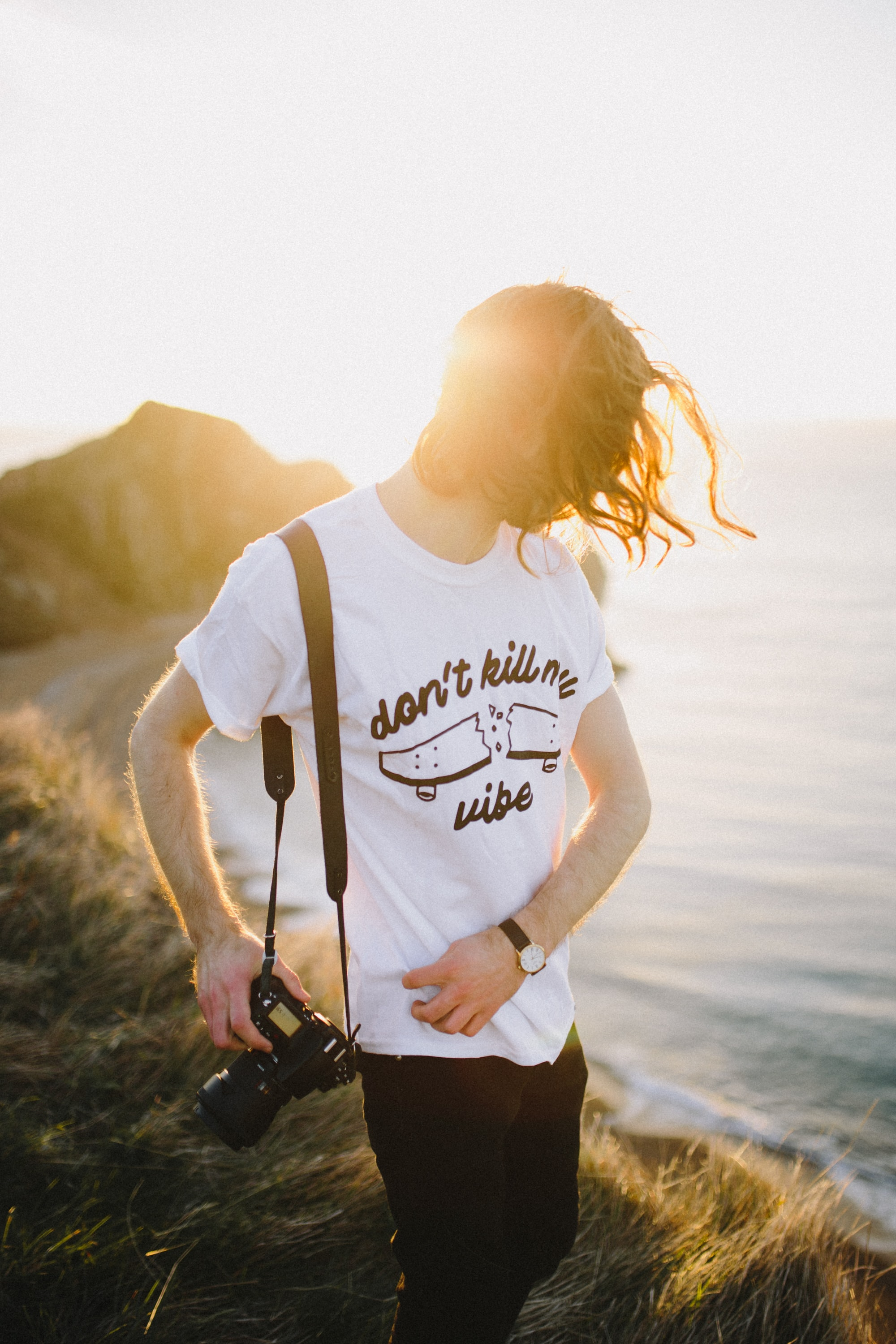 """A person with a camera on the seaside wears a t-shirt that says """"don't kill my vibe"""""""