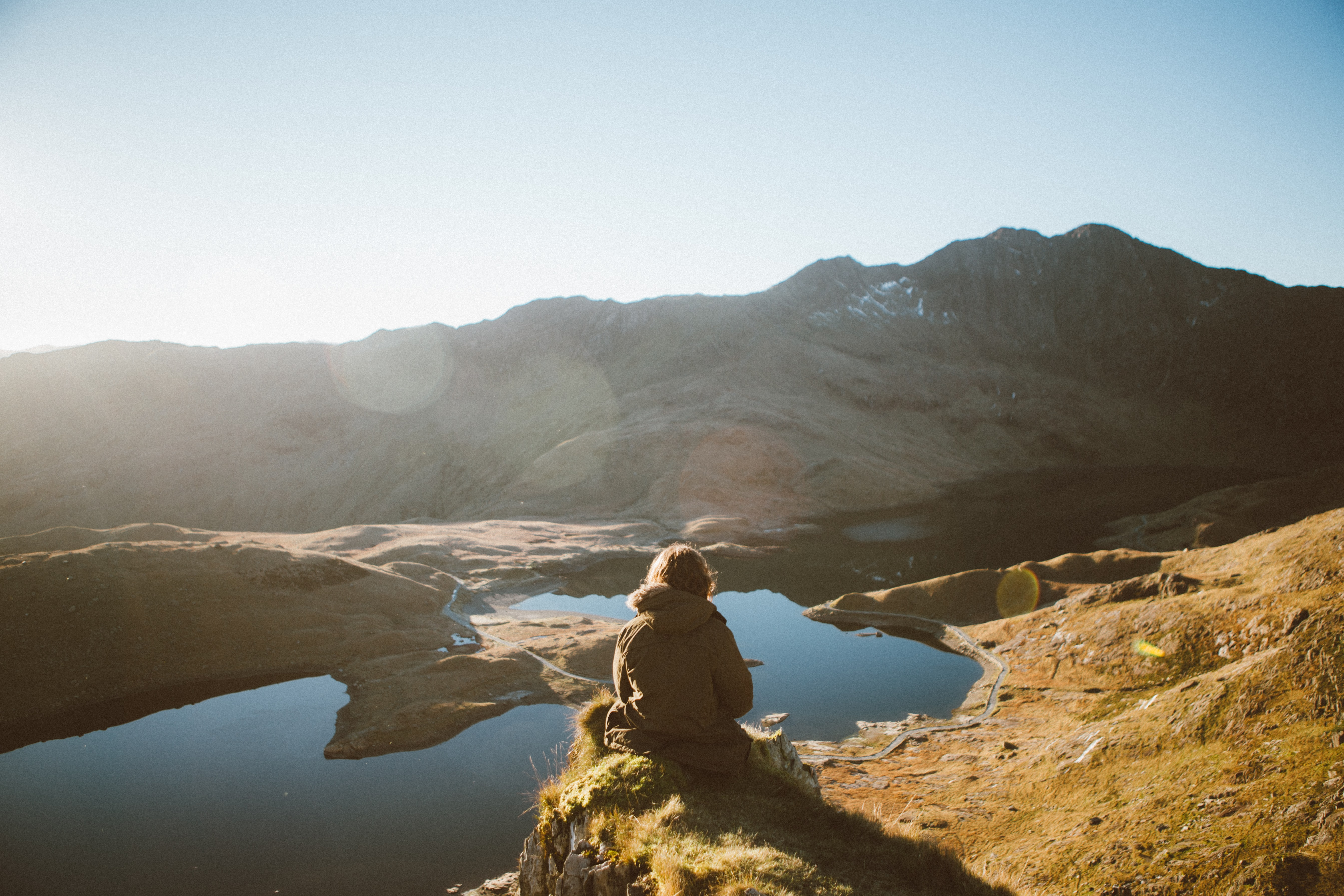 A person sitting on a ledge overlooking a mountain lake near Snowdon on a sunny morning