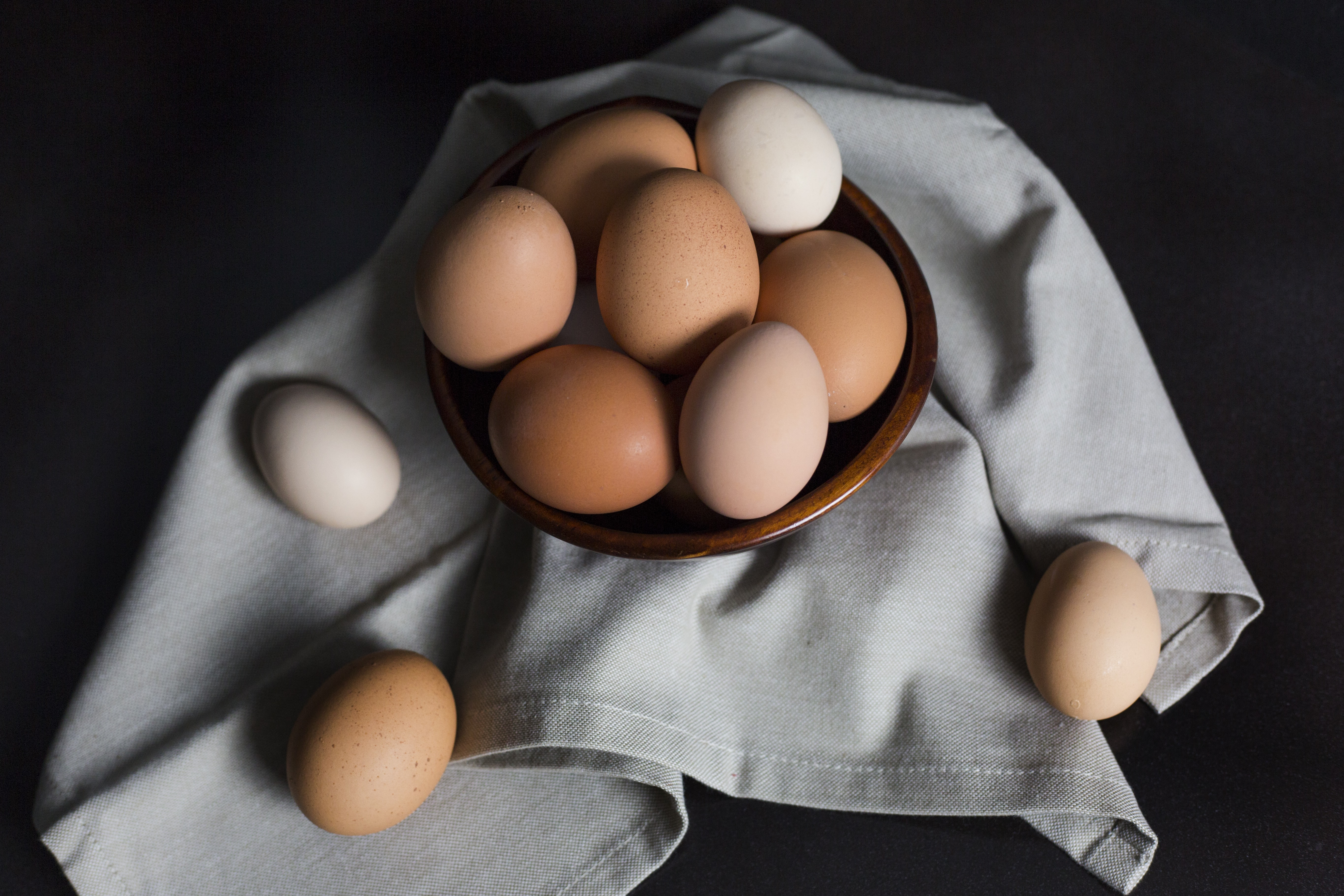 beige and white eggs on brown wooden bowl