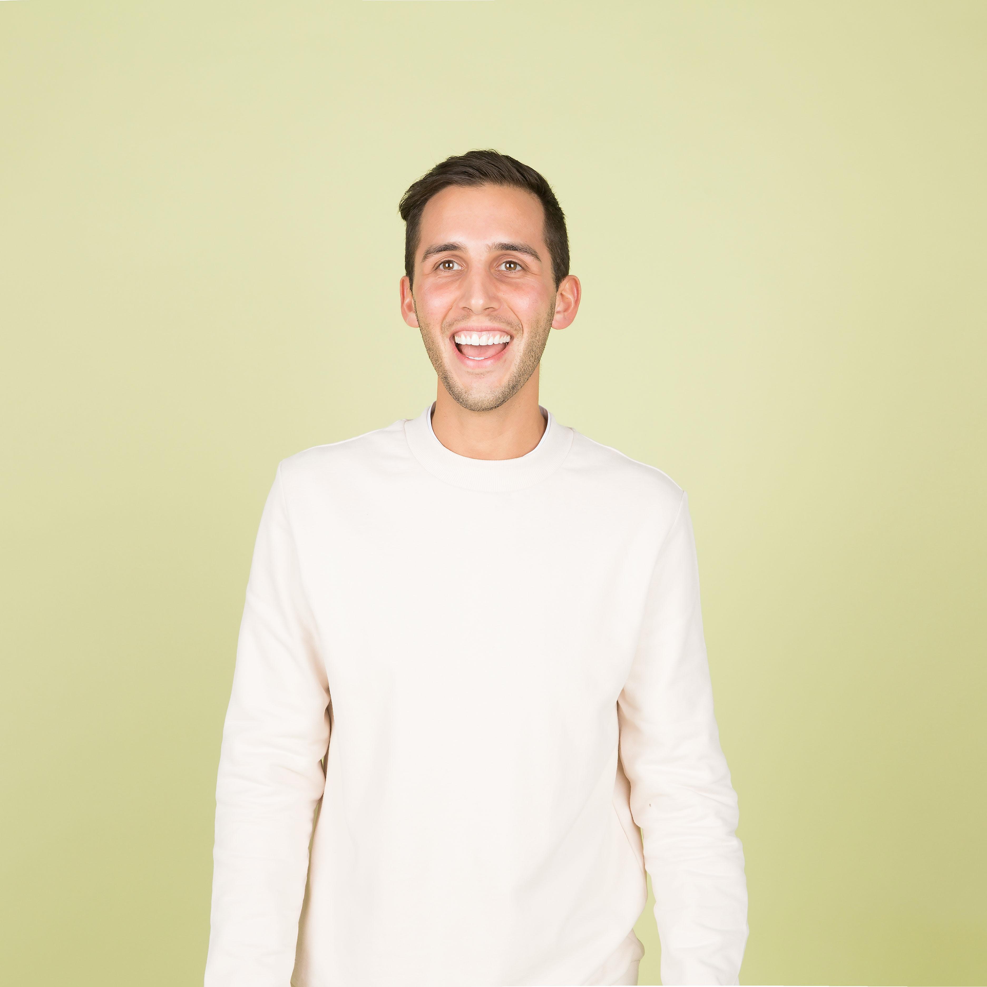 man wearing white crew-neck long-sleeved shirt standing inside well lighted room