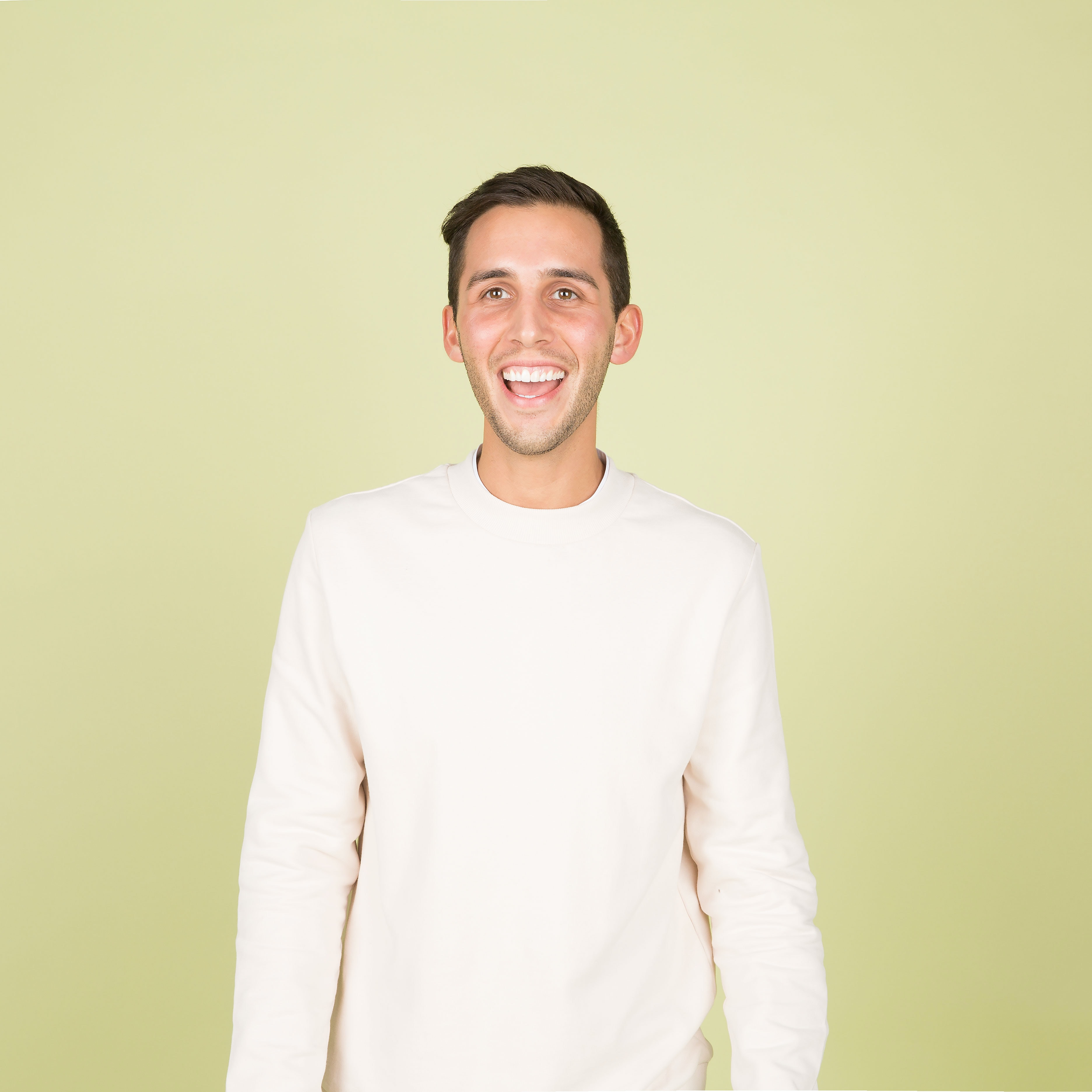 man wearing white crew-neck long-sleeved shirt standing inside well lighted room