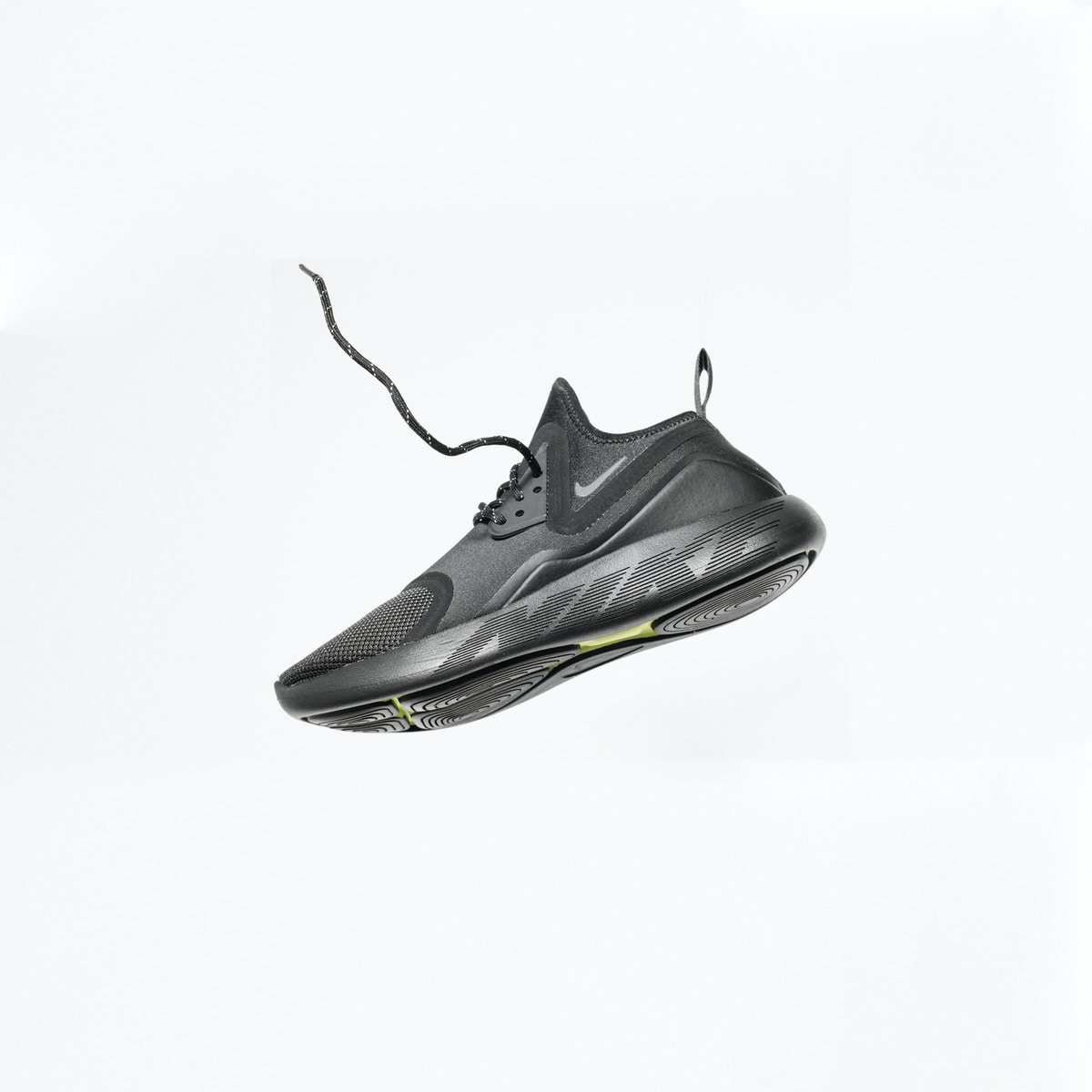 A black Nike sneaker falling the lace looks like a worm jumping out of a hole