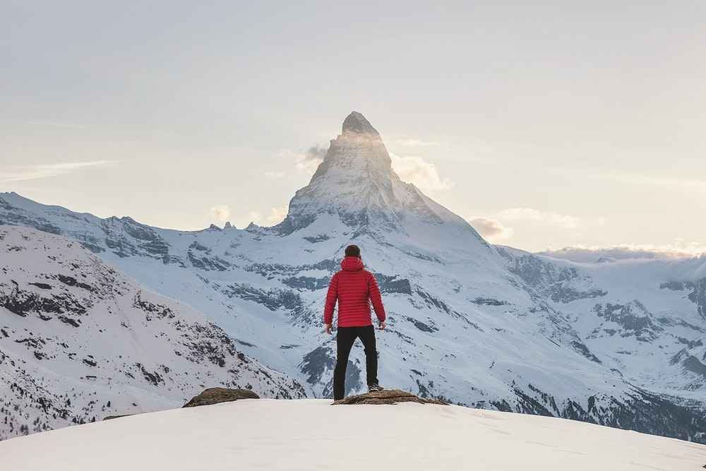 person in red hoodie standing on snowy mountain during daytime