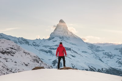 person in red hoodie standing on snowy mountain during daytime mountain teams background