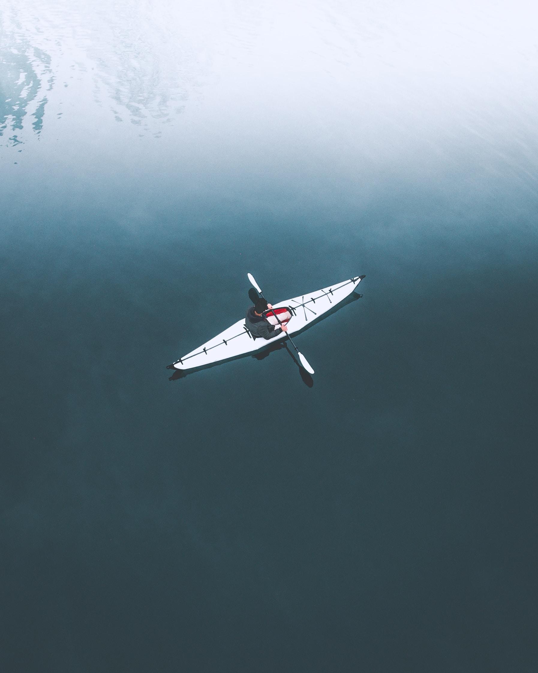 man in kayak on body of water during daytime