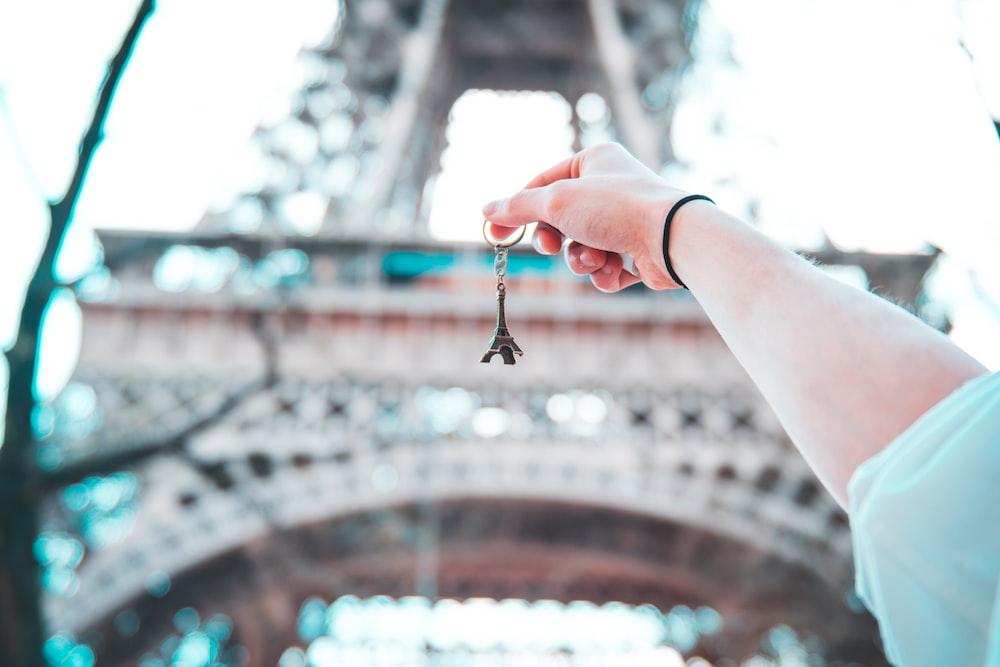 person holding Eiffel Tower keychain