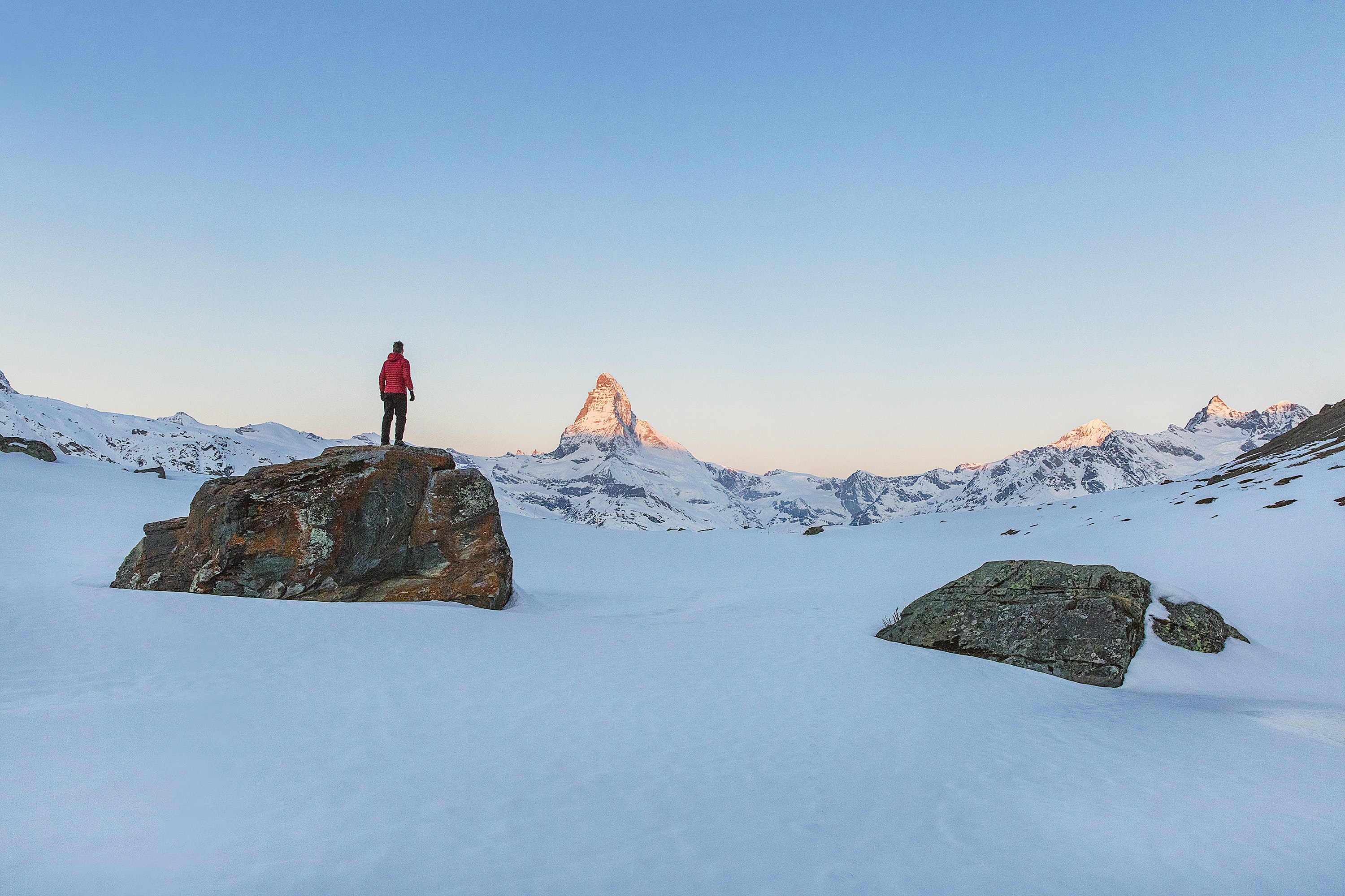 A man standing on a tall rock at the alps in Zermatt, Switzerland