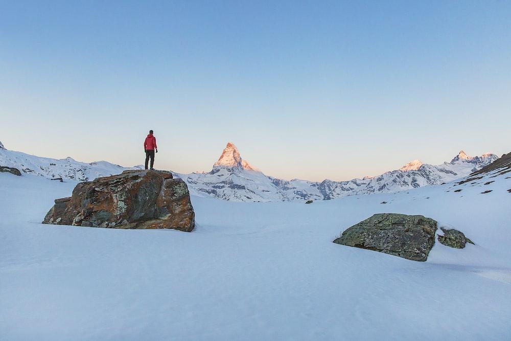 man standing on rock during daytime