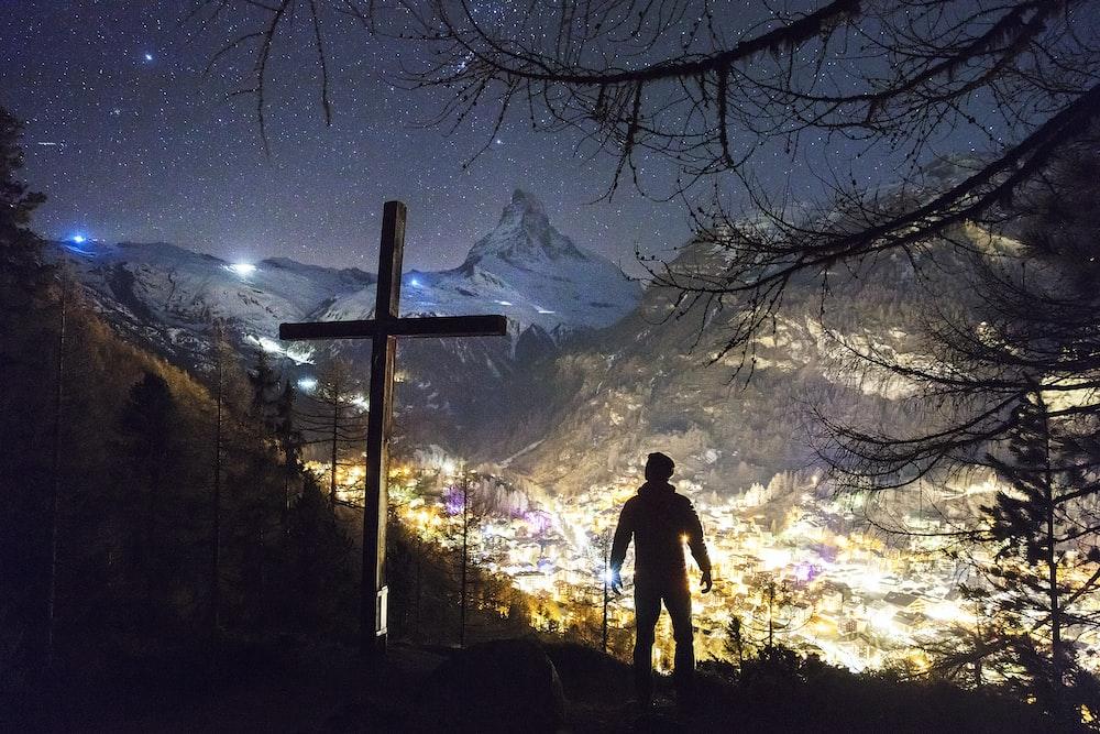 man standing near cross during night