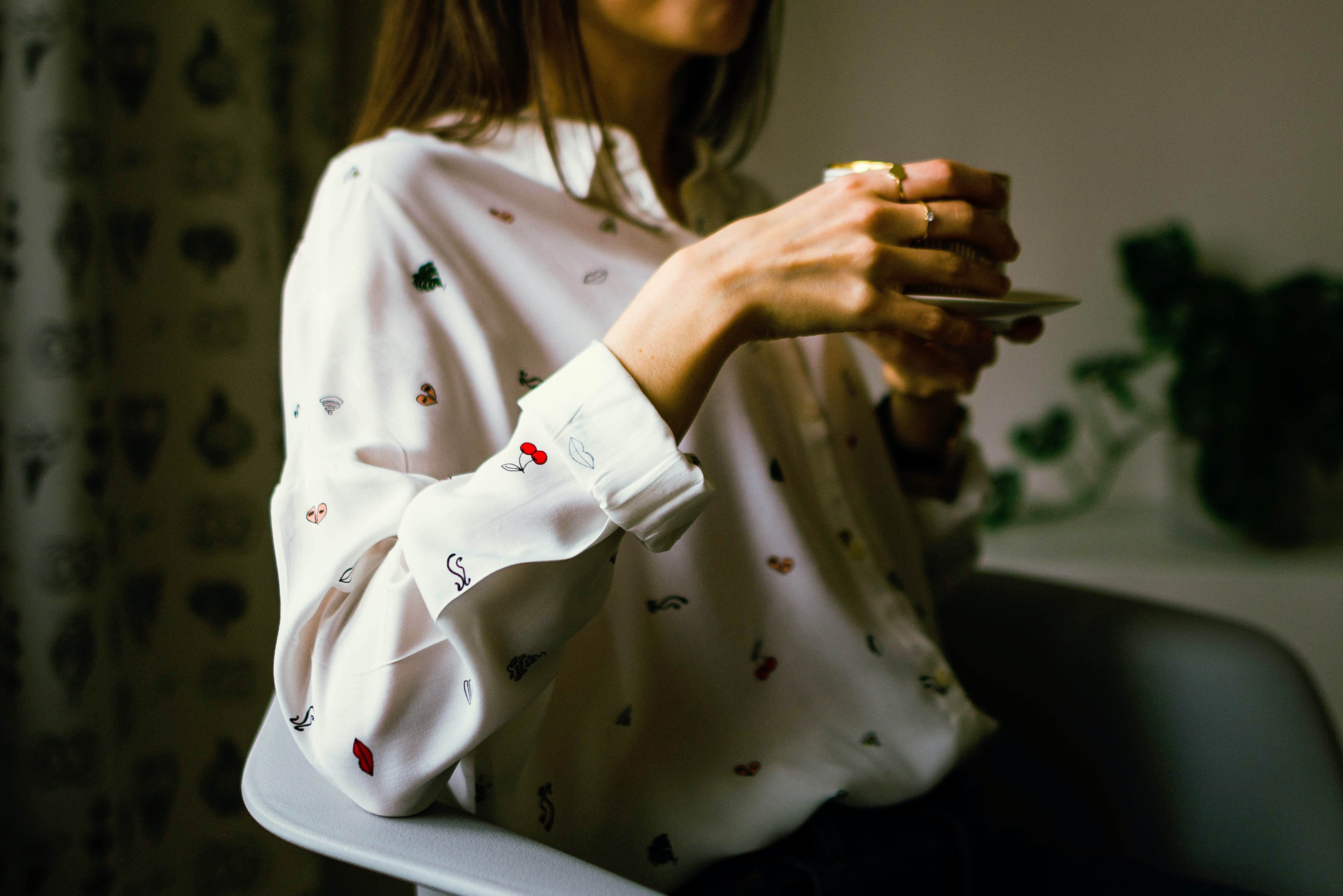 woman in white long-sleeved collared shirt holding teacup