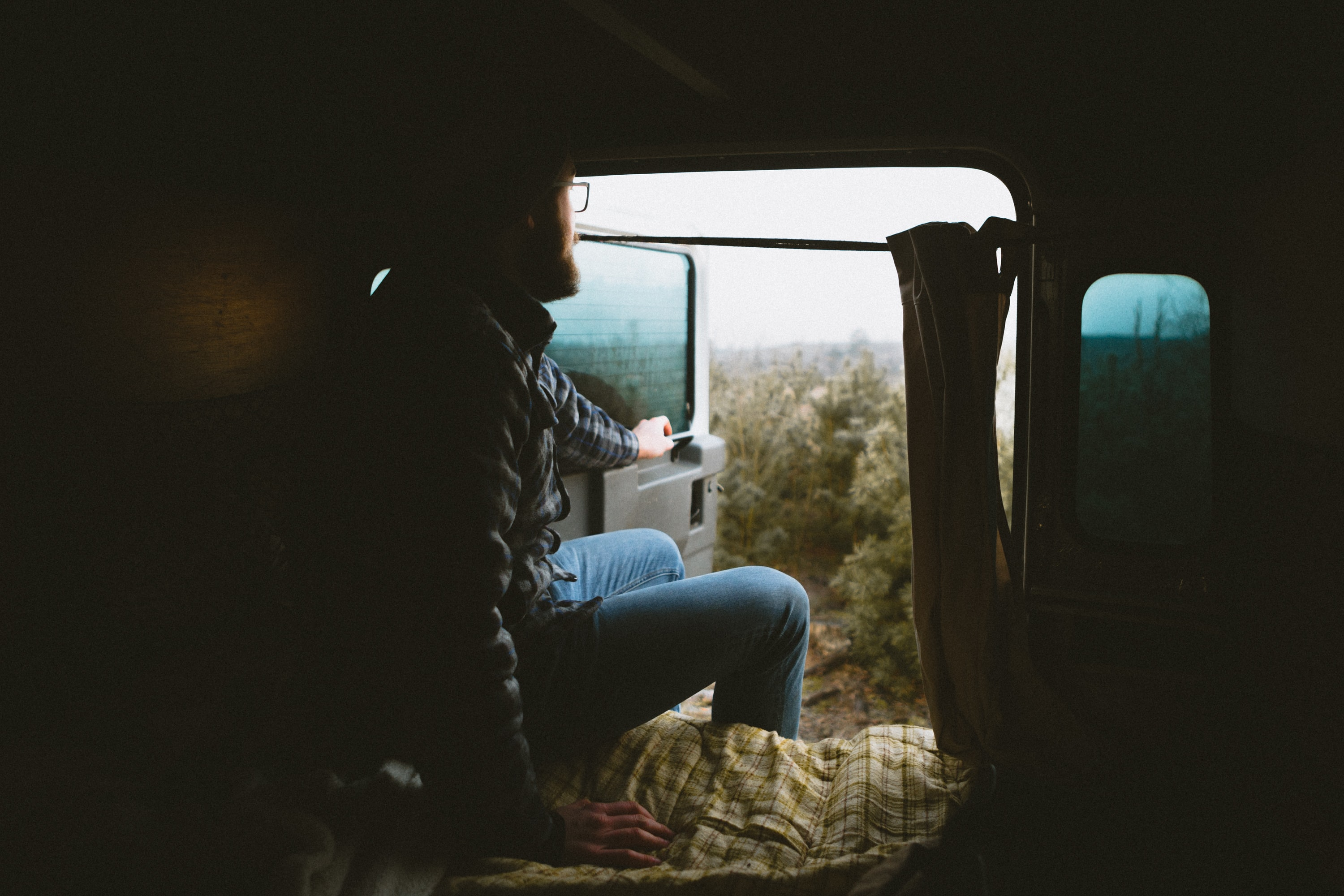 Man wearing vintage clothes sitting in an open van on a roadtrip