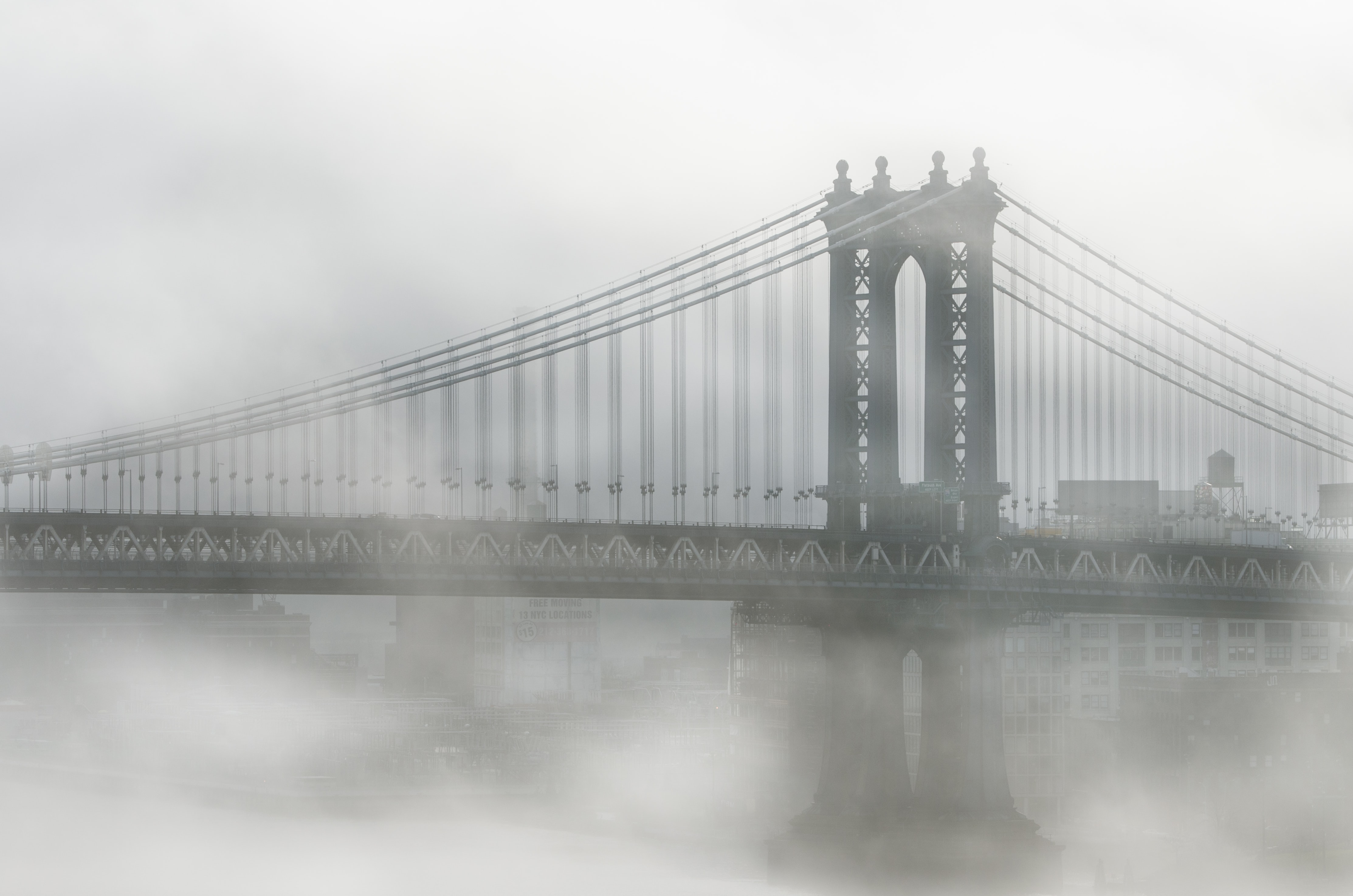 Brooklyn Bridge covered in mist on a foggy morning