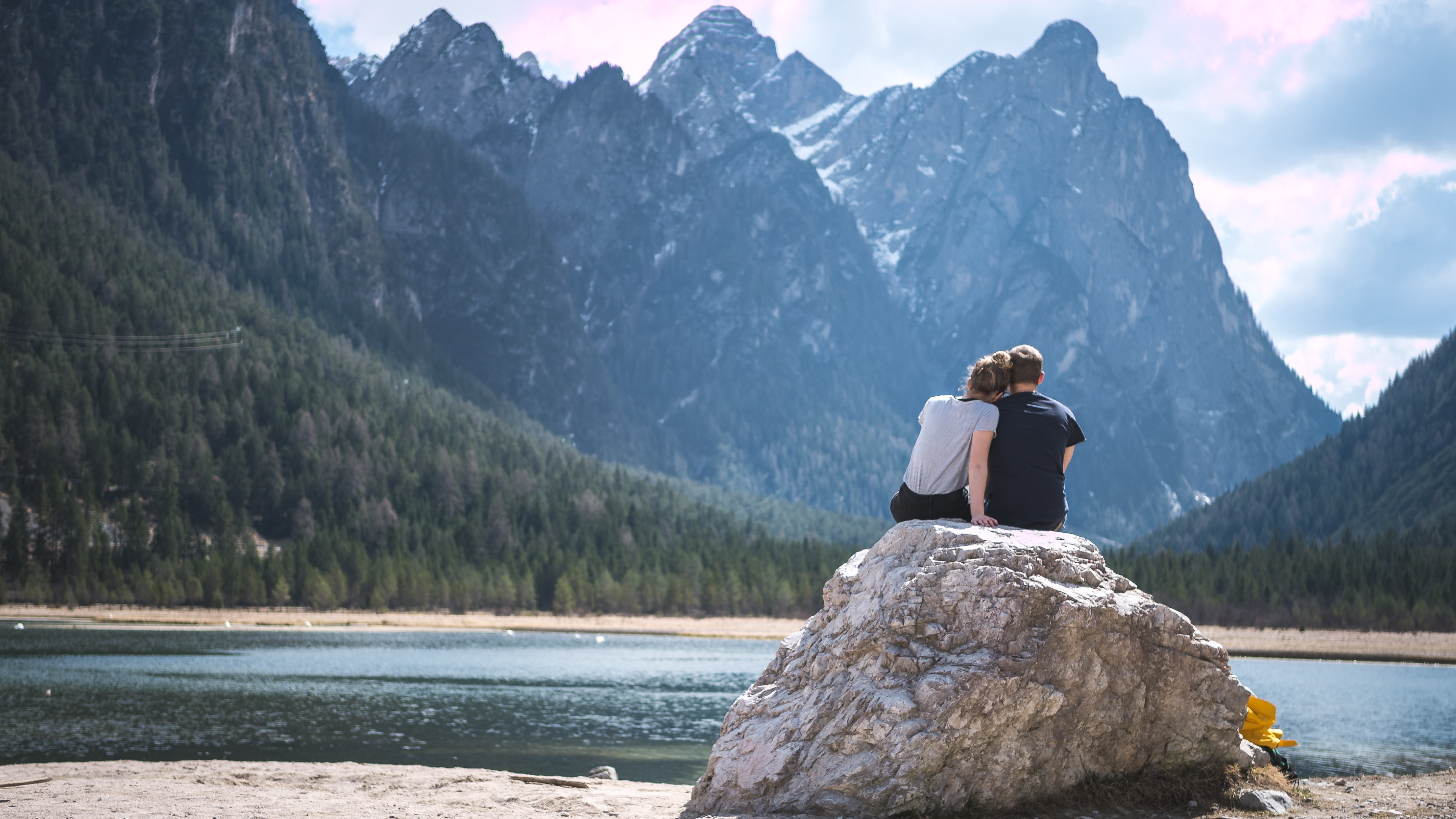 man and woman sitting on rock near body of water and mountain during daytime