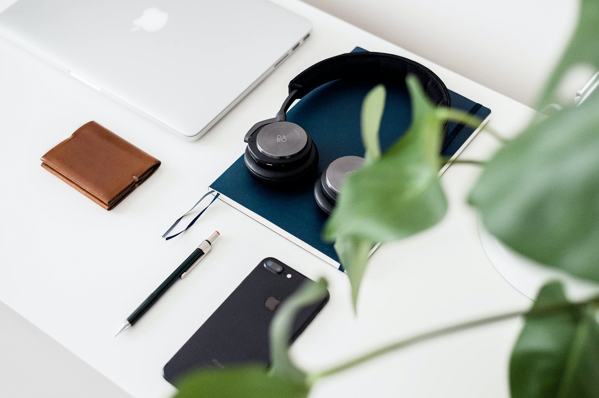 Arrangement of headphones, a phone, a laptop, a notebook, a wallet and a pen on a white desktop