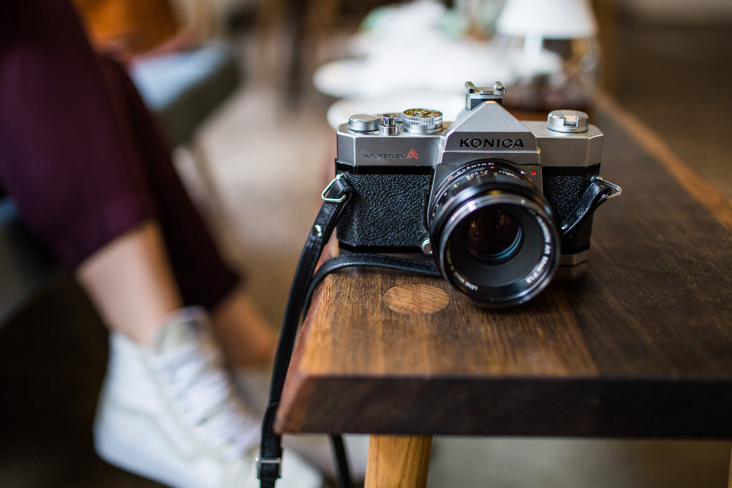 Konica Autoreflex camera on wooden table besides a woman sitting down