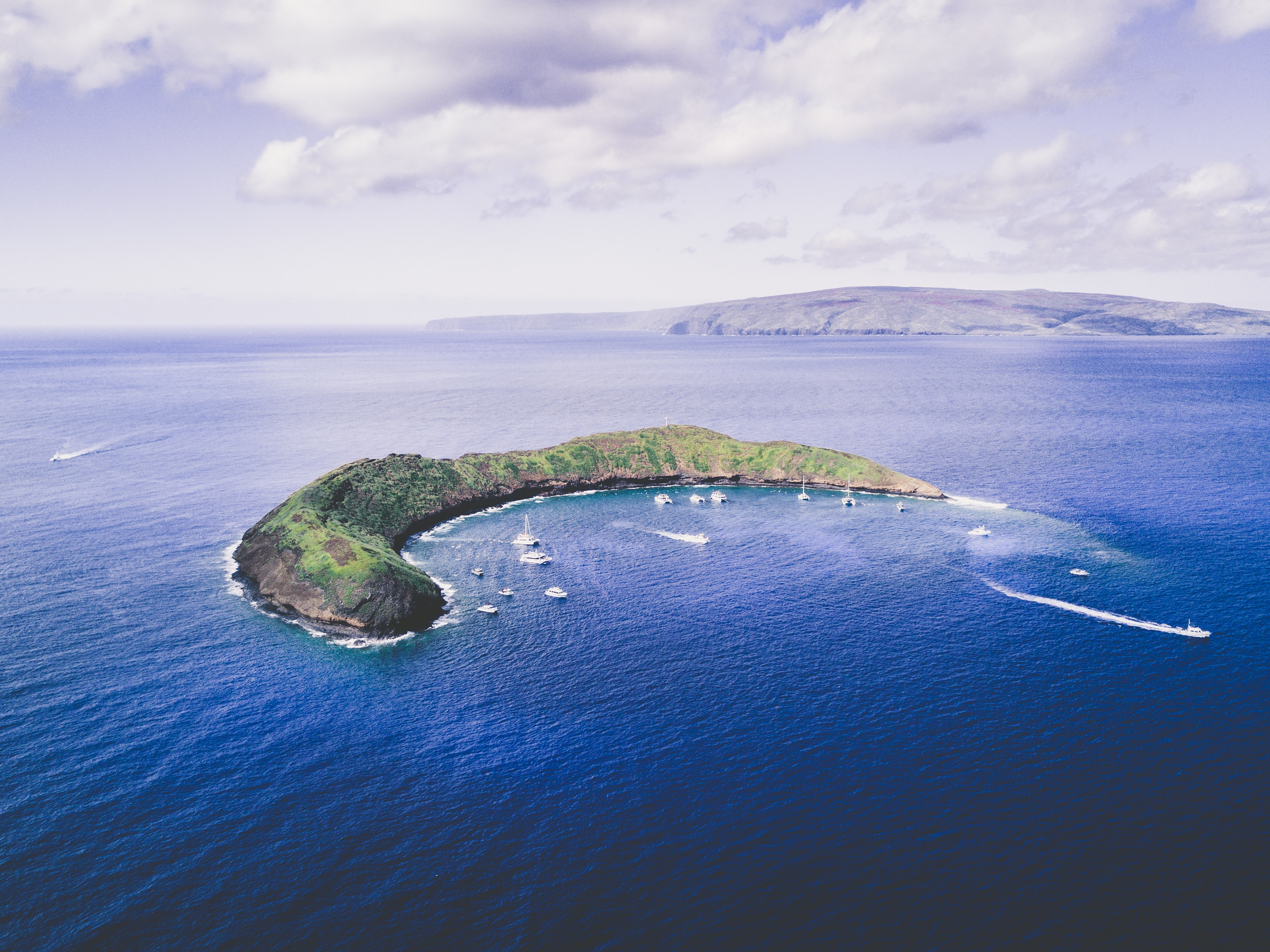 A crescent moon shaped island in the middle of a bright blue ocean at Molokini Crater