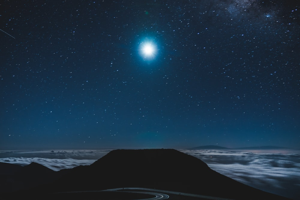 silhouette photo of body of water under blue sky at night