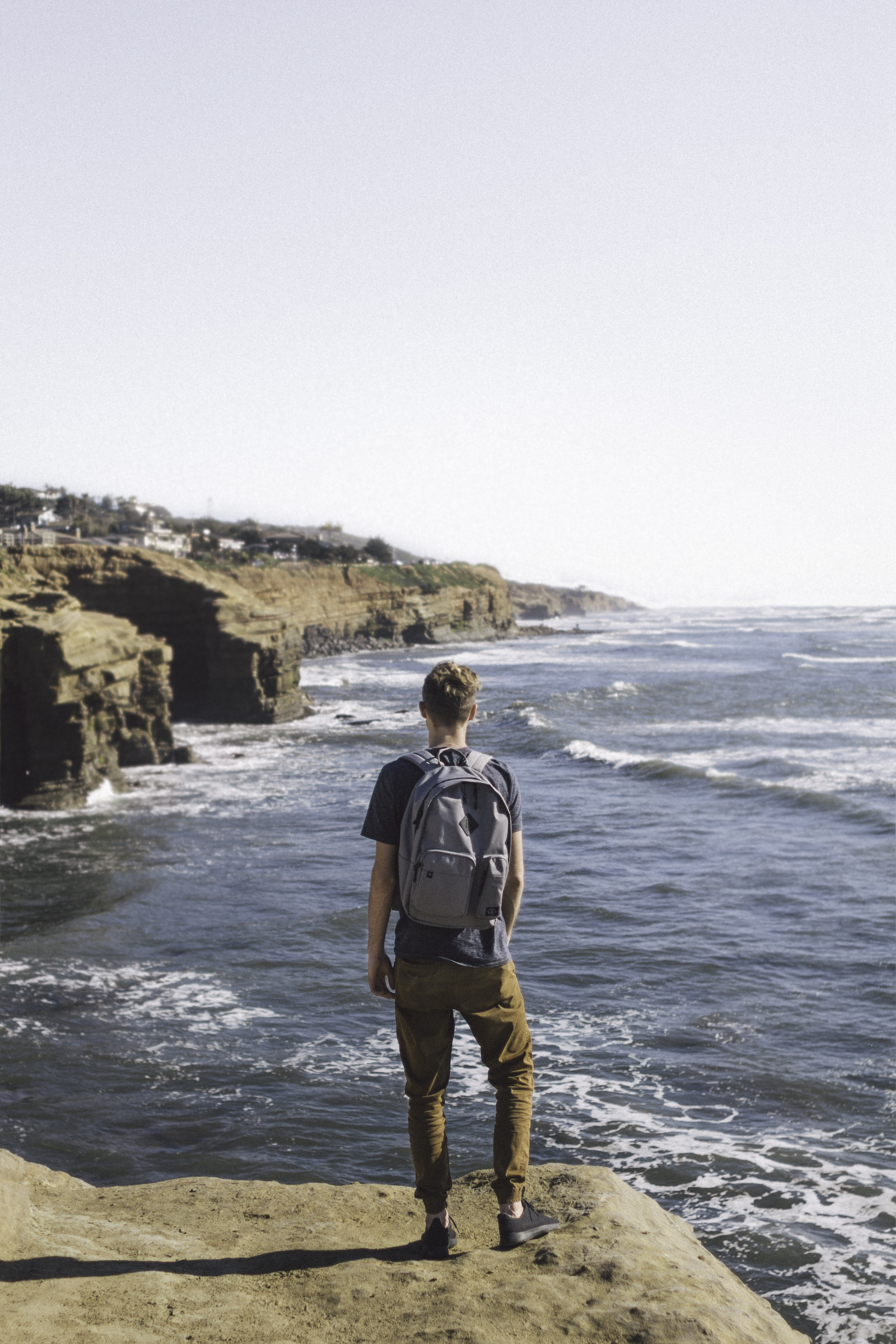 Man in pants with backpack stands by Sunset Cliffs