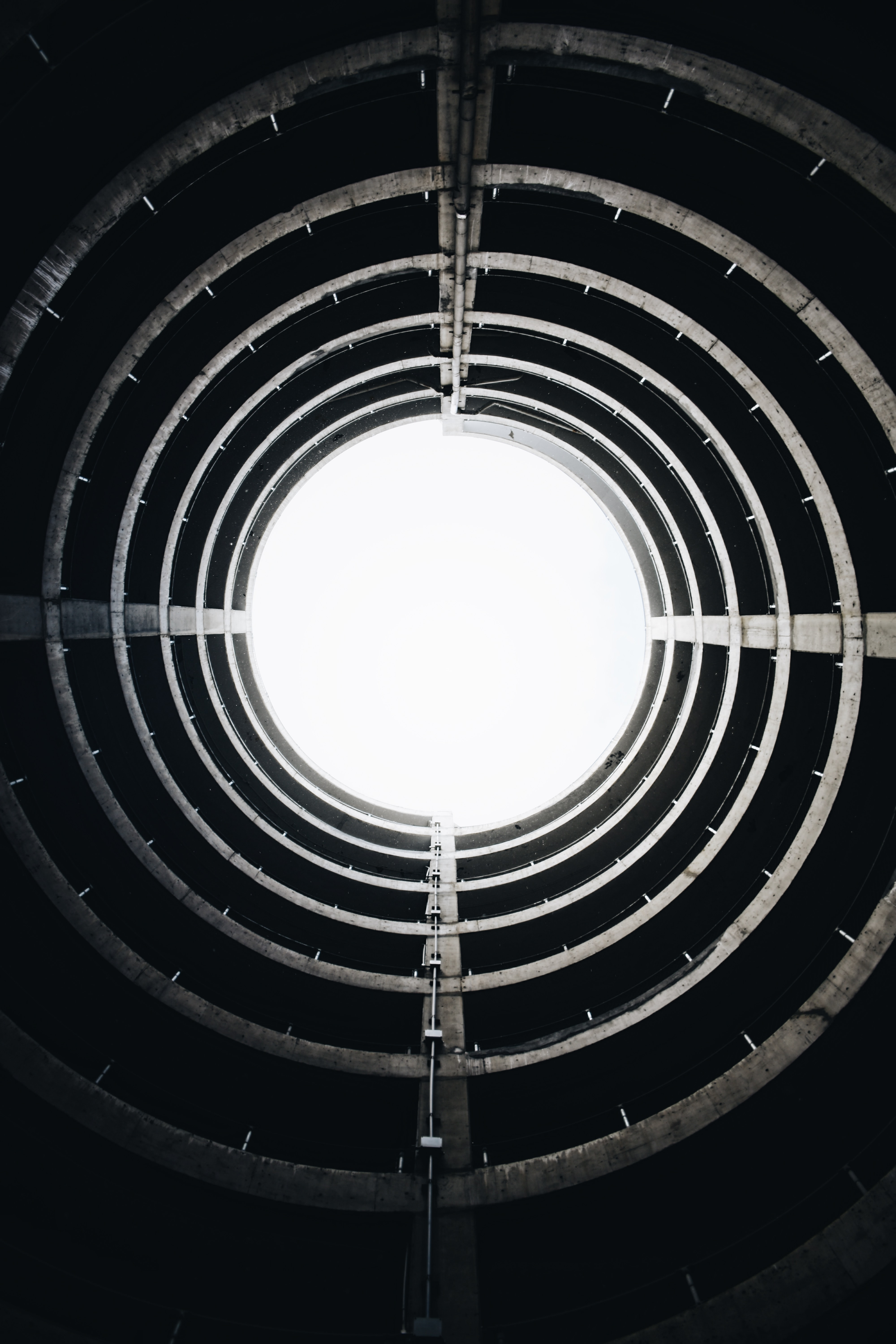 Black and white shot of circular spiral circular architecture from below with sky light