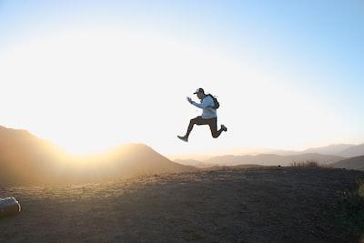 大自然で朝日のまえでジャンプしている若者