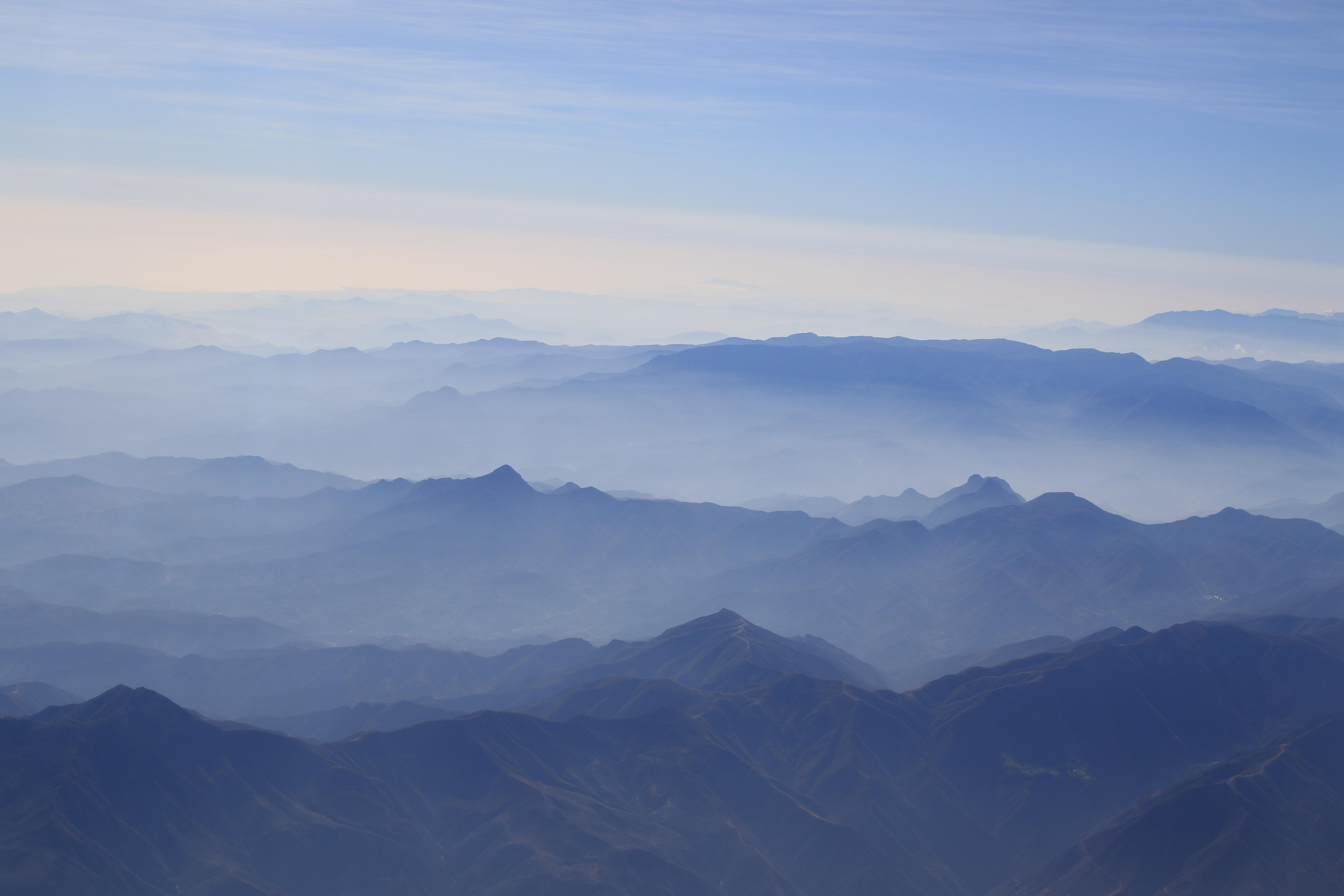 A vast landscape dominated by hazy blue mountain folds